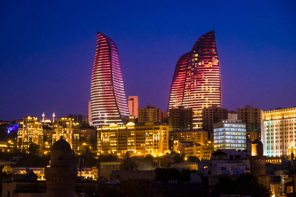 The flame towers of Baku, Azerbaijan, at night: the sky is dark blue and the towers illuminate with red and yellow flames snaking up the building.