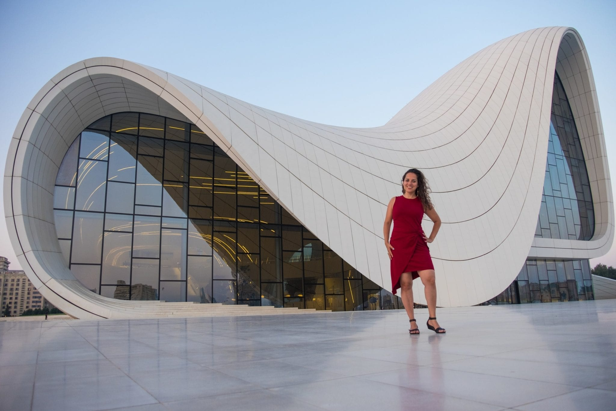 Kate poses in a red dress in front of the white swooping curvy roof and glass wall of the Heydar Aliyev Center in Baku, Azerbaijan.