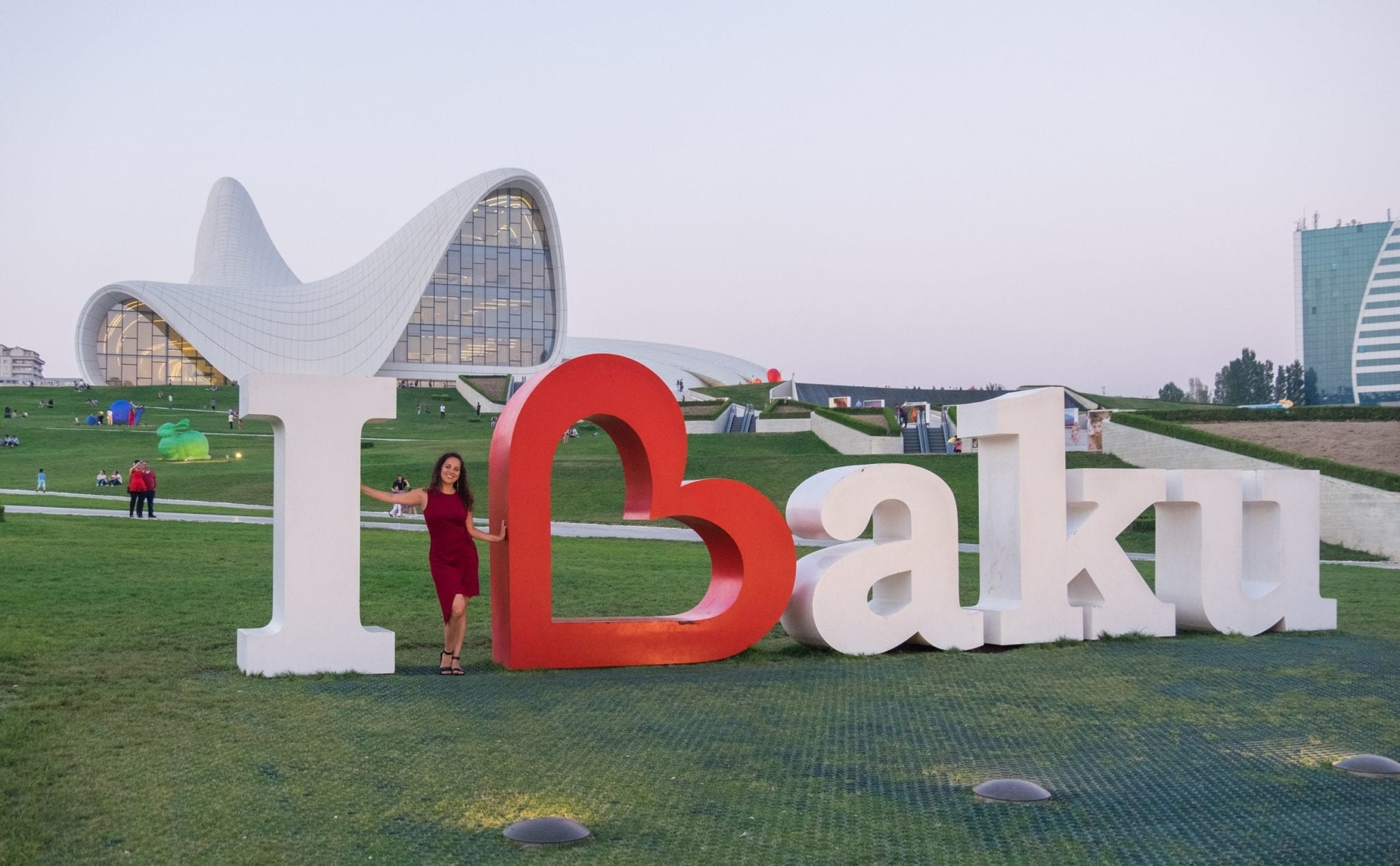 """Kate stands in the middle of an """"I Love Baku"""" sign where the B is shaped like a heart. In the background is the swooping white roof of the Heydar Aliyev Center."""
