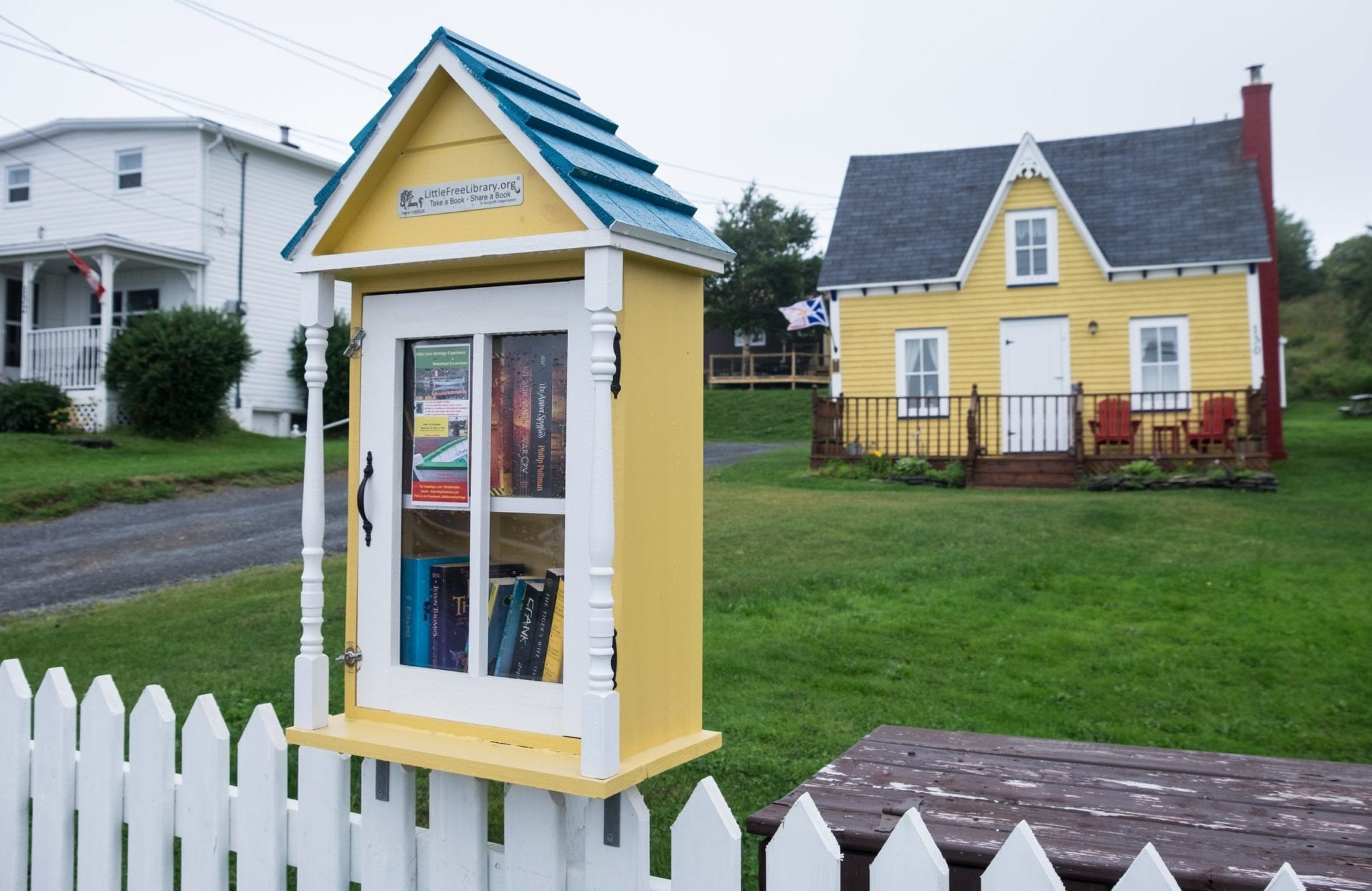 A yellow little library built on a white picket fence with books behind the glass door. In the background, a matching yellow cottage.