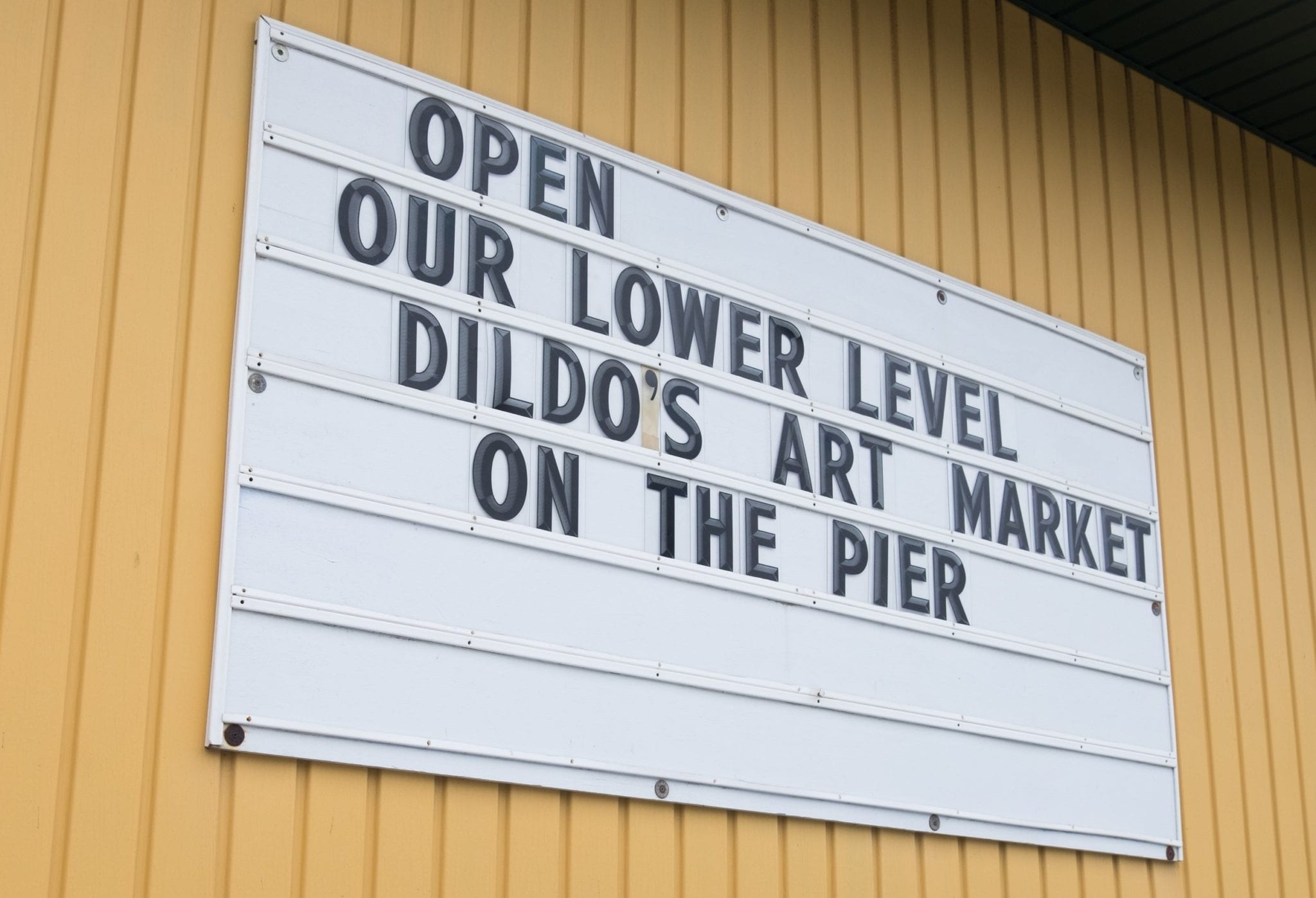 "A sign that reads ""Open! Our lower level. Dildo's Art Market on the Pier."""