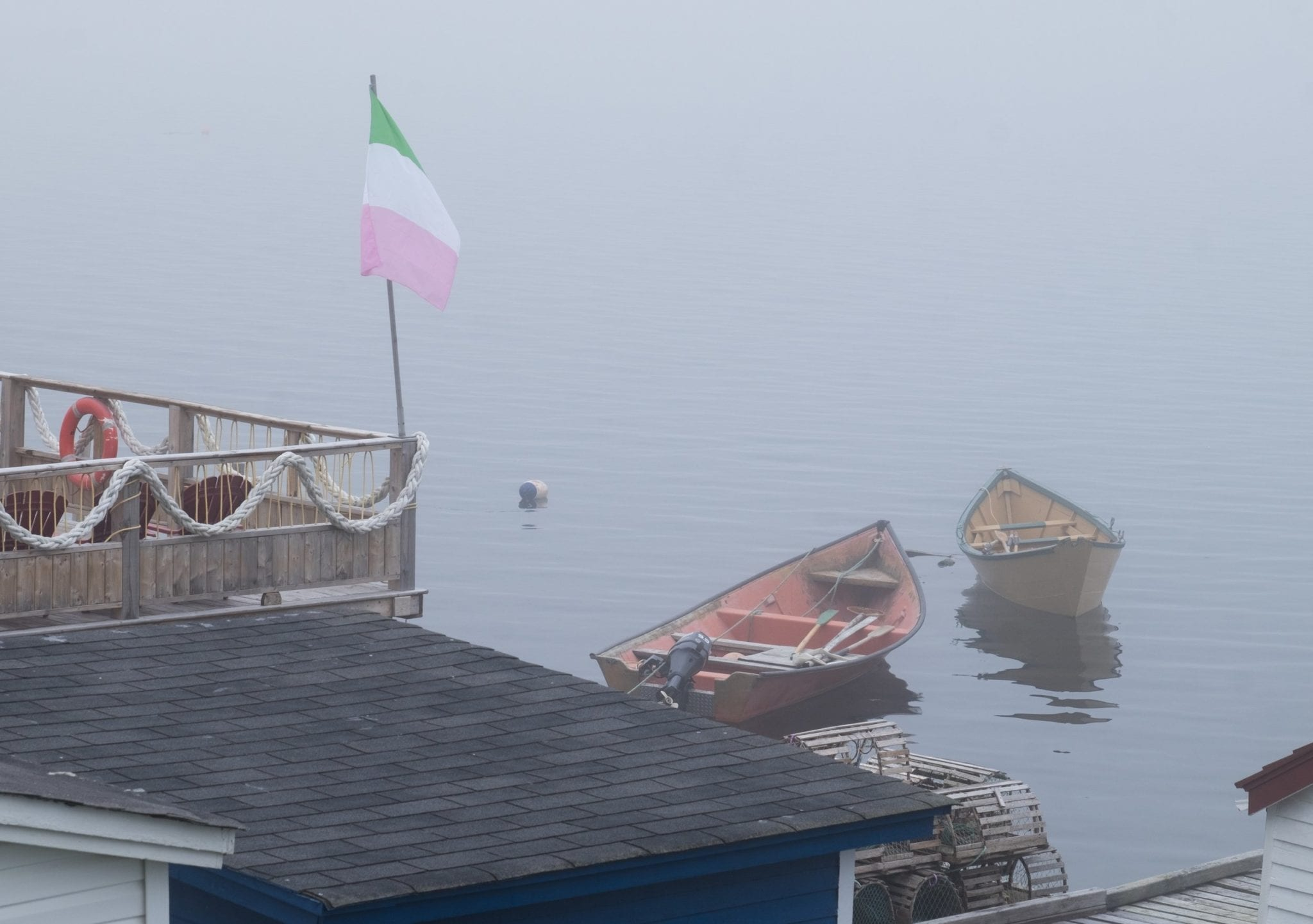 Rowboats in a foggy gray harbor. A flagpole with the green, white and pink Newfoundland independence flag on top.
