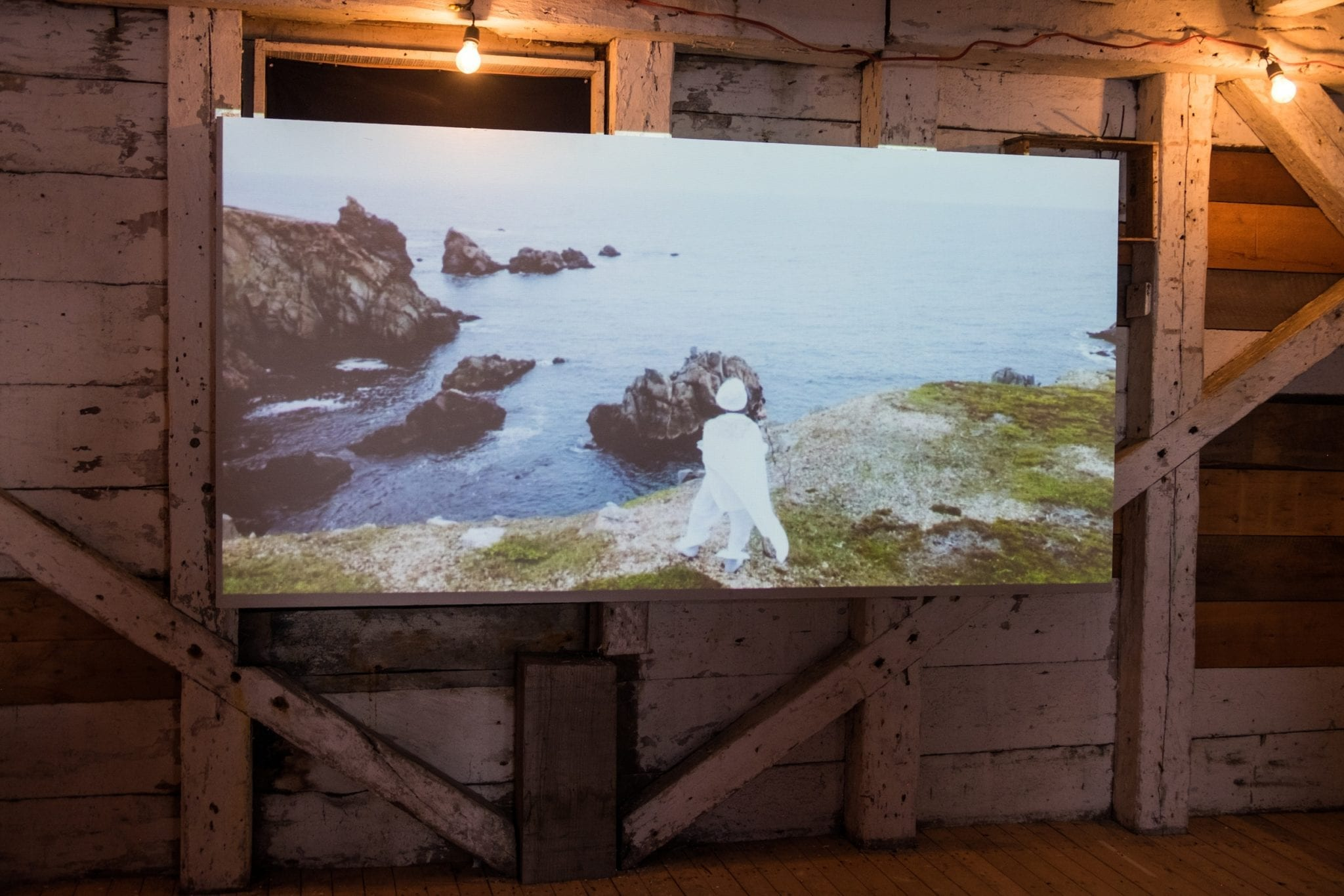 A screen with a woman in white African costume and a turban, standing on the edge of a cliff in Newfoundland.