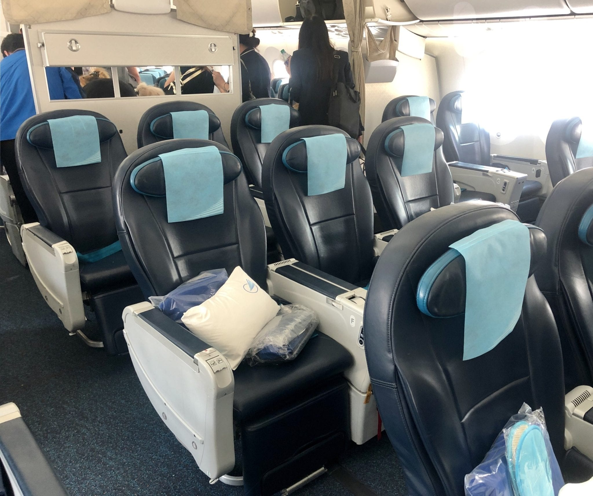 Inside view of an Azerbaijan Airlines flight, Comfort Club. Larger dark blue metal seats separated by thick armrests with pillows and blankets.