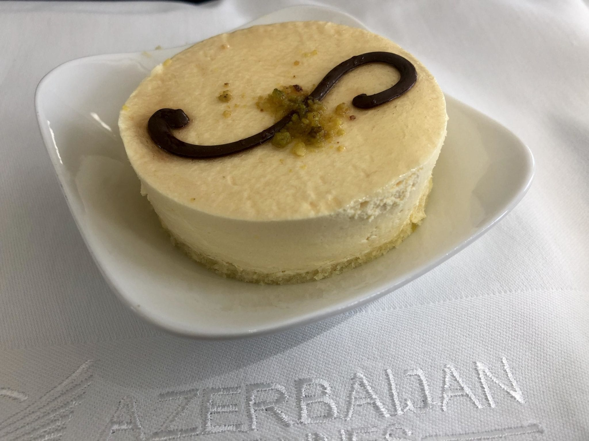 A cheesecake topped with a chocolate swirl in the Azerbaijan Airlines Comfort Club.
