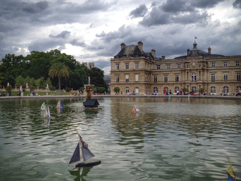 What are the best neighborhoods in Paris? A view of the pond in the Luxembourg Gardens, a sailboat in the water, gray clouds overhead.