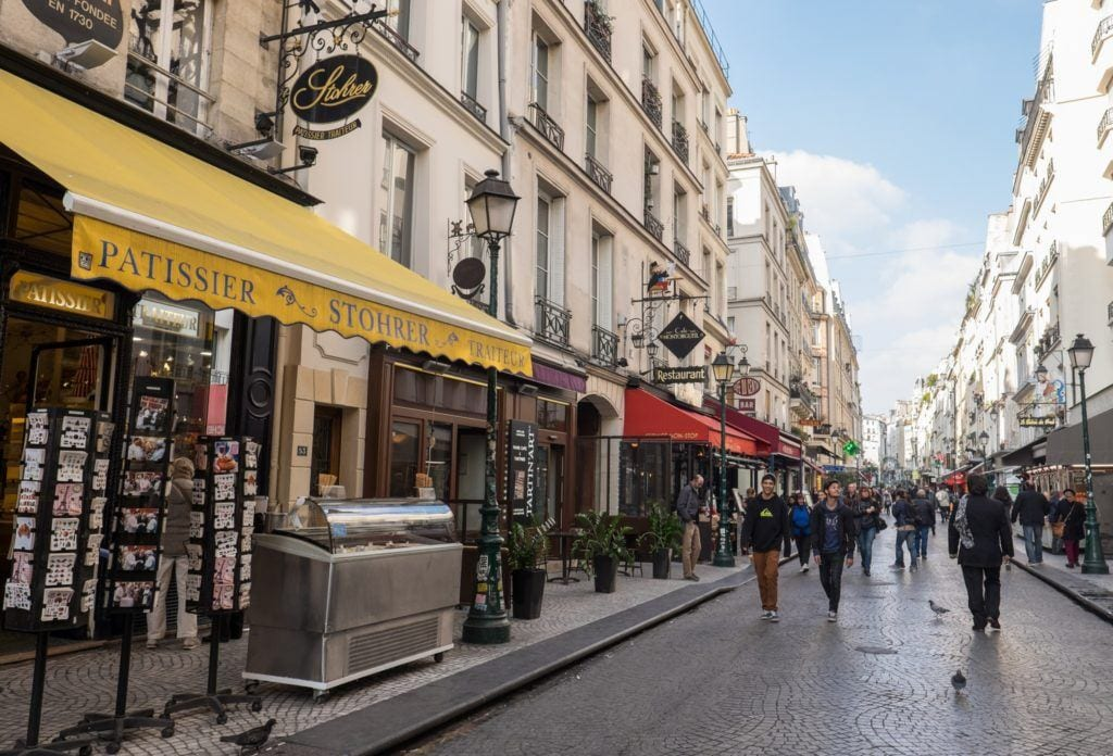 Rue Montorgueil in Paris, lined with food shops and people walking down the street. In front is a shop with a bright yellow awning.