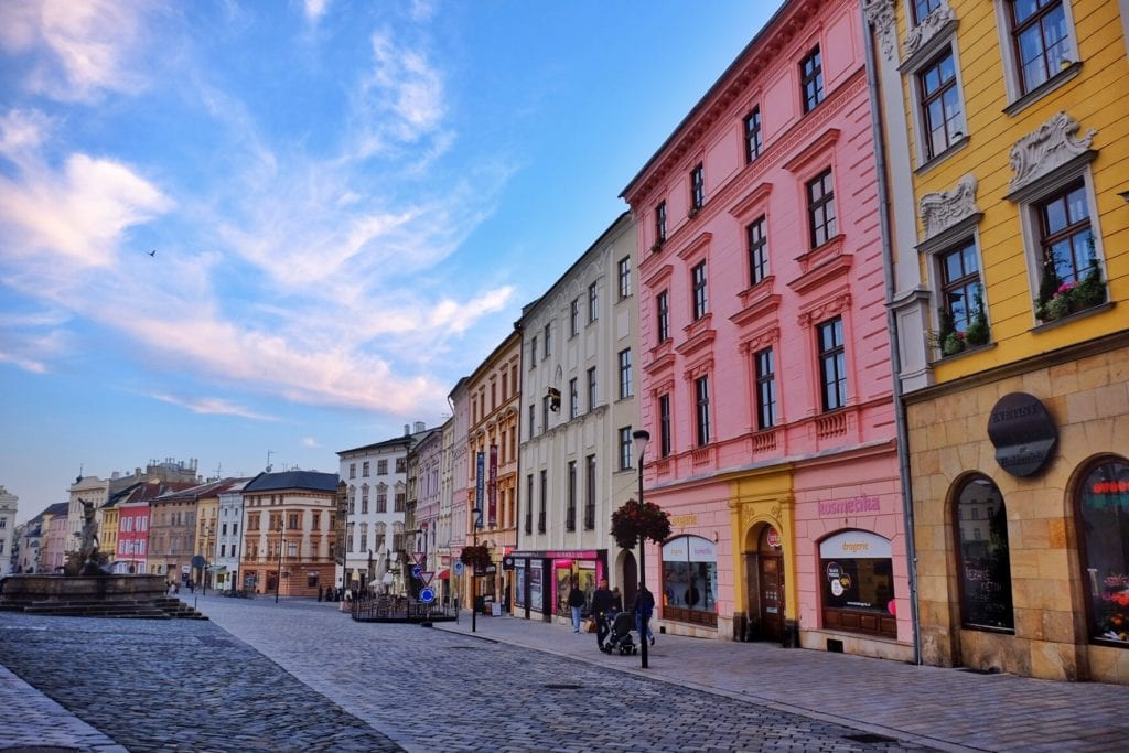 Bright pink and yellow buildings of Olomouc set against a bright blue sky.