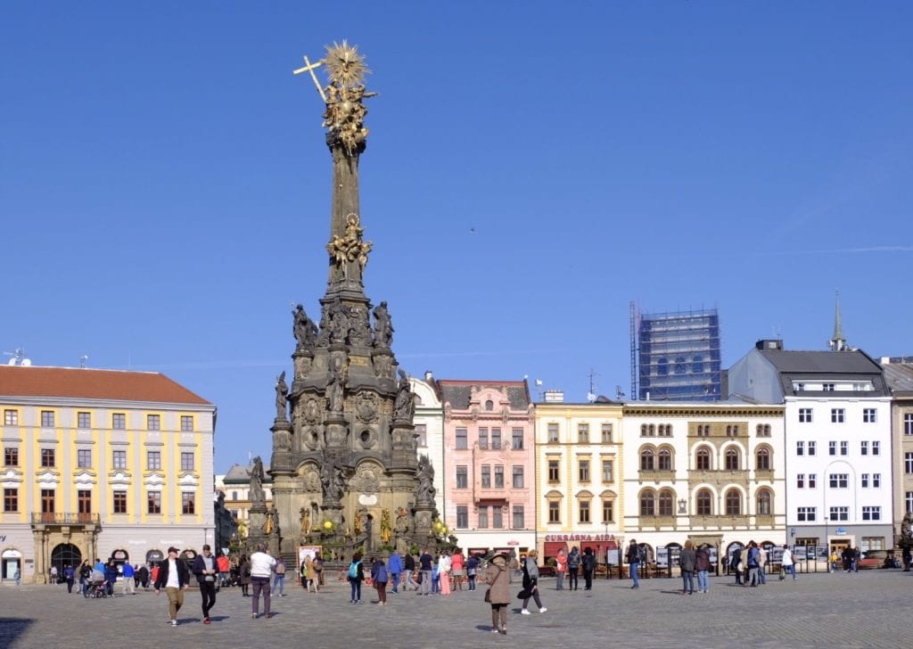 The UNESCO Column in Olomouc, Czech Republic, rising high in the middle of a square surrounded by pastel-colored buildings.