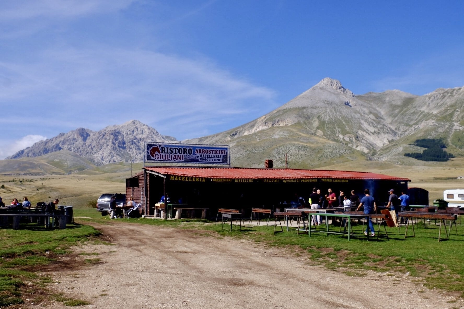 A butcher shop with smoking grills in front of it, in the middle of nowhere in Abruzzo, Italy. Incredible mountains rise in the background underneath a blue sky.