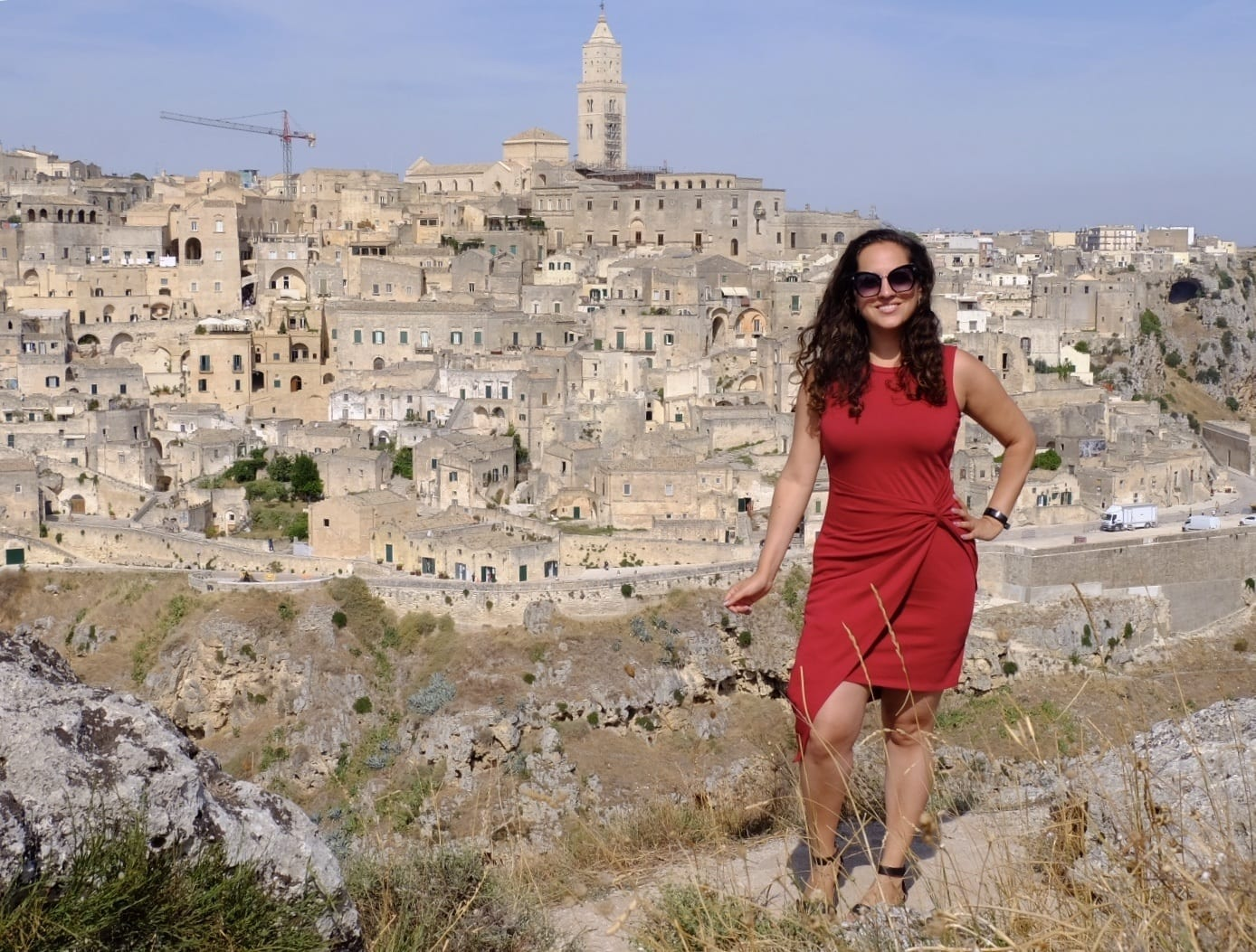 Kate wears a red dress with an asymmetrical hemline and poses in front of the city of Matera: stone towers and homes built on top of a row of sassi (caves).