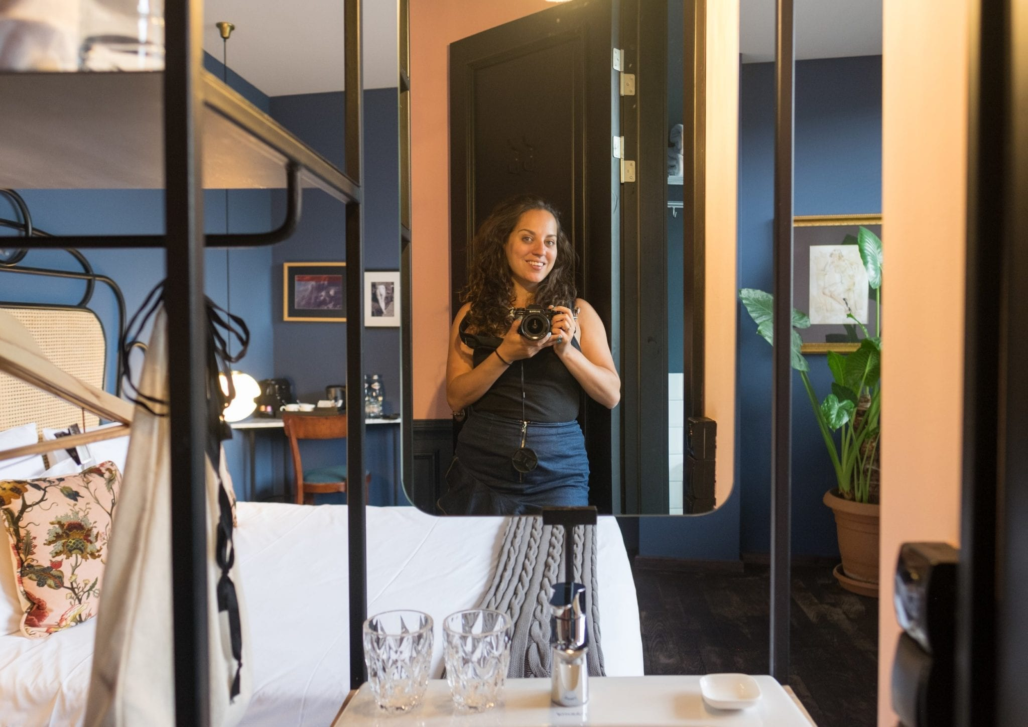 Kate takes a photo in a small mirror above a tiny modern sink; in the background you can see a modern hotel room painted dark blue.
