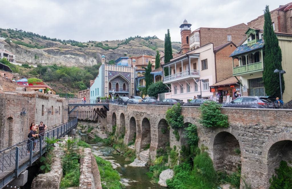 A street scene in Tbilisi's Bath District, with an ancient bridge on one side, people taking photos from a modern iron walkway, and buildings rising up on the hills on each side.