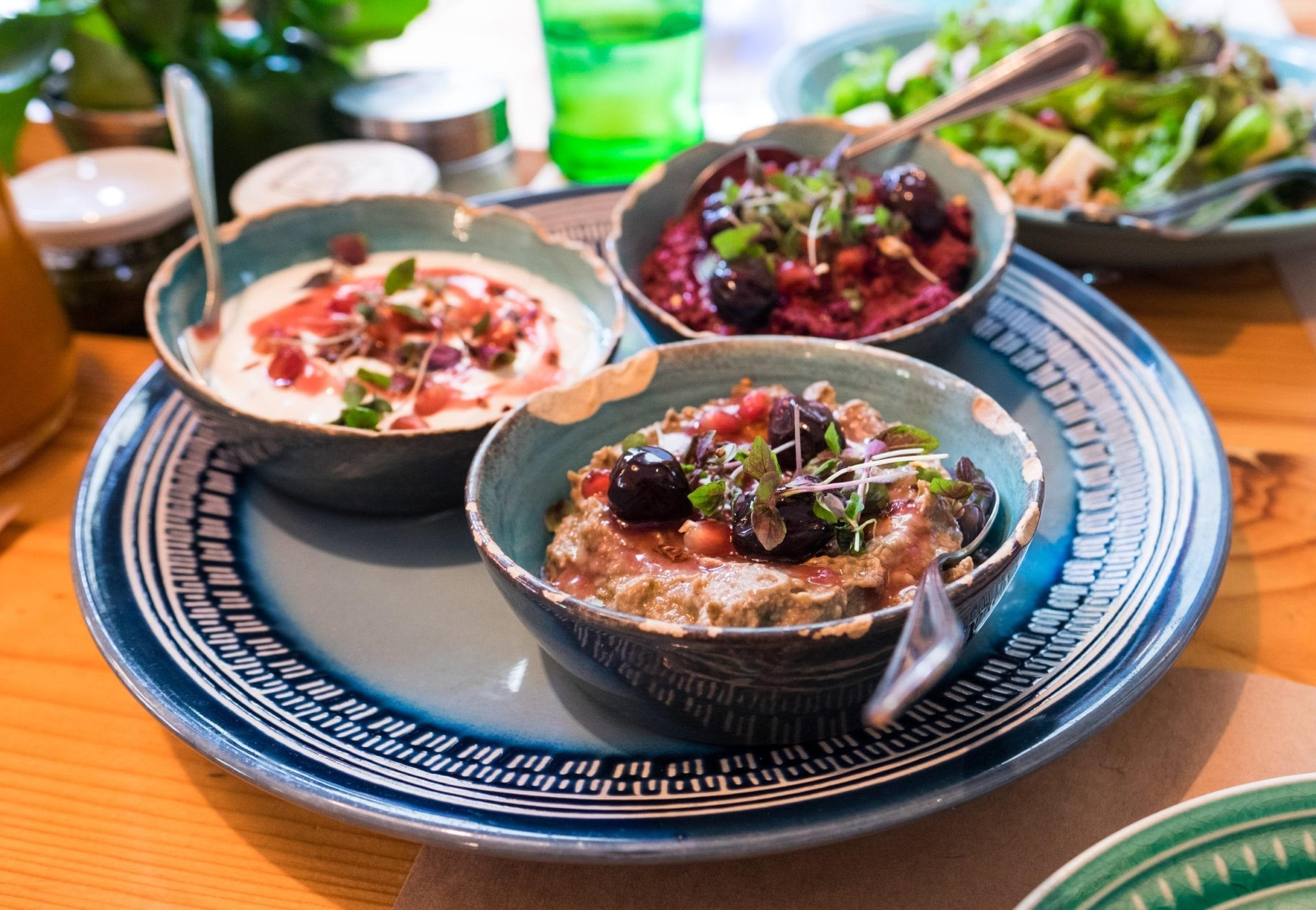 A plate covered with three tiny bowls, each filled with a different kind of Georgian walnut dip, topped with parsley.