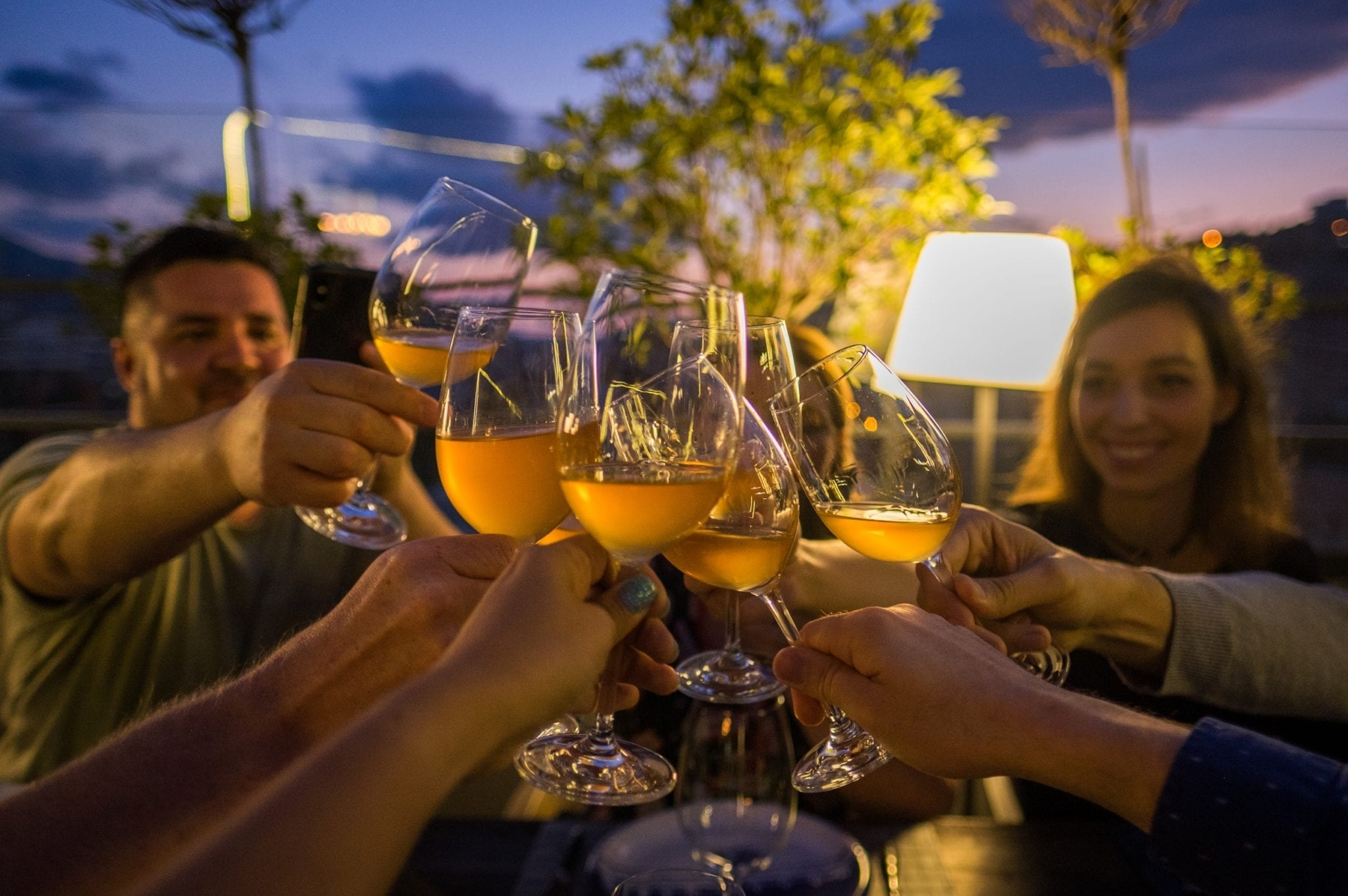 Several hands toasting glasses of orange wine in front of a blue and purple sunset sky.