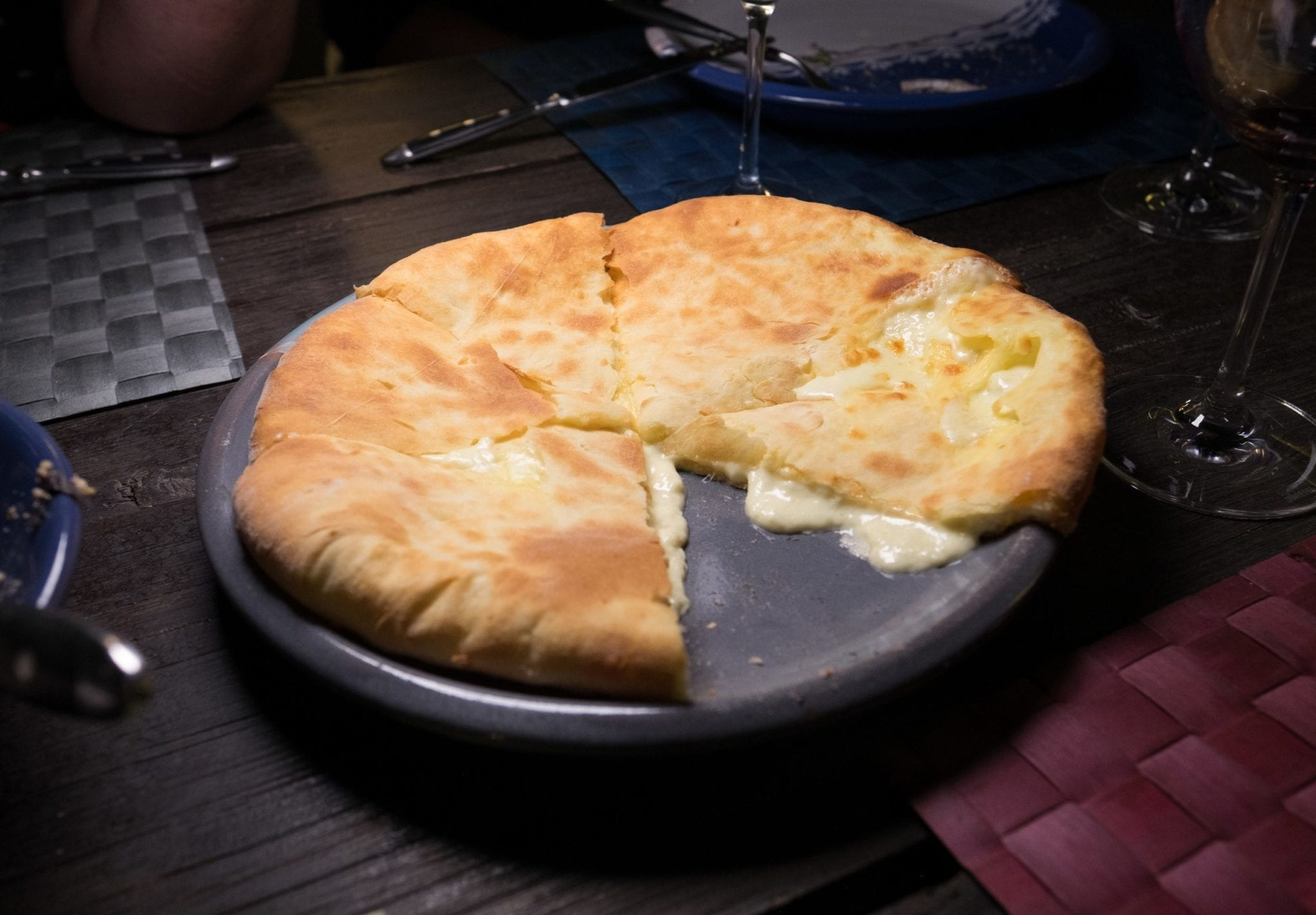 A khachapuri (Georgian cheese pie) with one slice missing, the cheese oozing out.