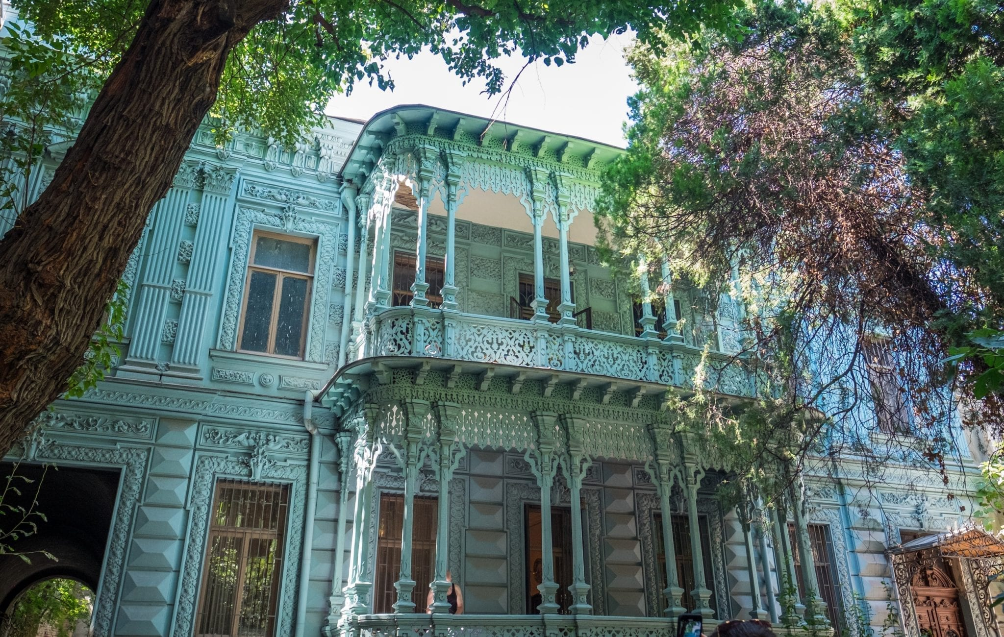 A pale blue house with light sea green trim on the balcony, surrounded by trees.