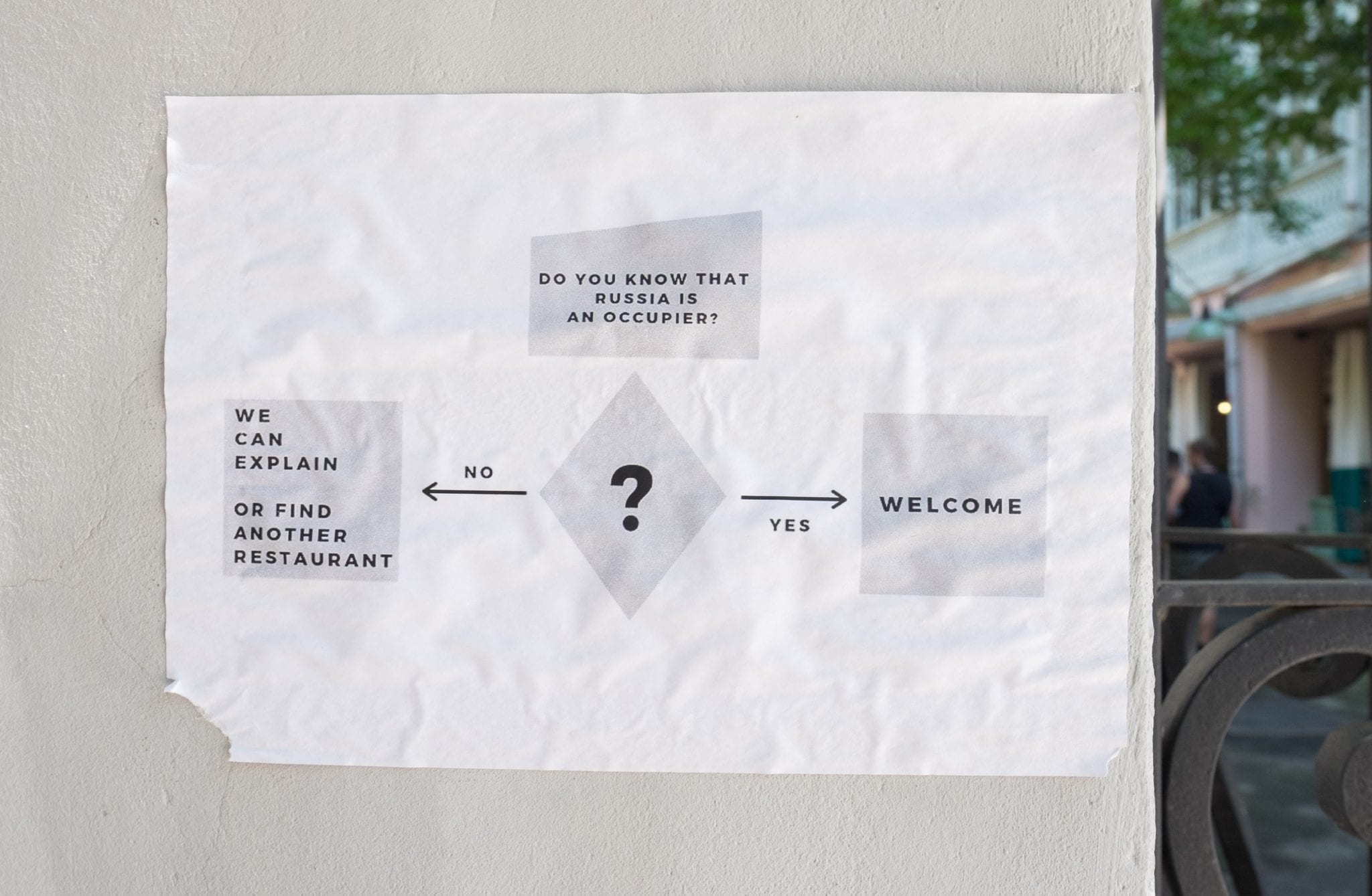"""A sign with a flow chart reading, """"Do you know that Russia is an Occupier?"""" If yes, """"Welcome."""" If no, """"We can explain or find another restaurant."""""""