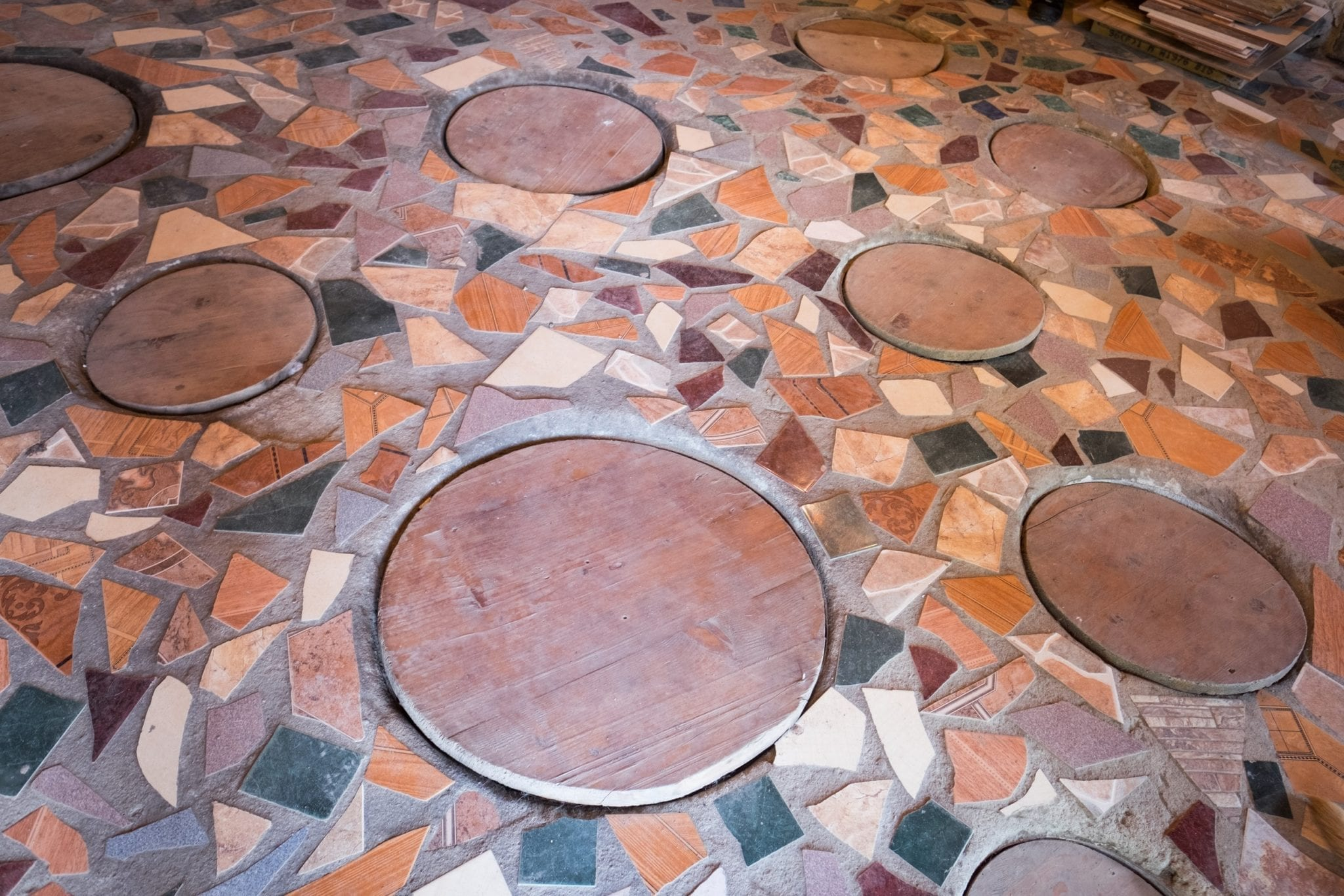 Round holes in a tiled floor where the Georgian qvevri wine is fermented.