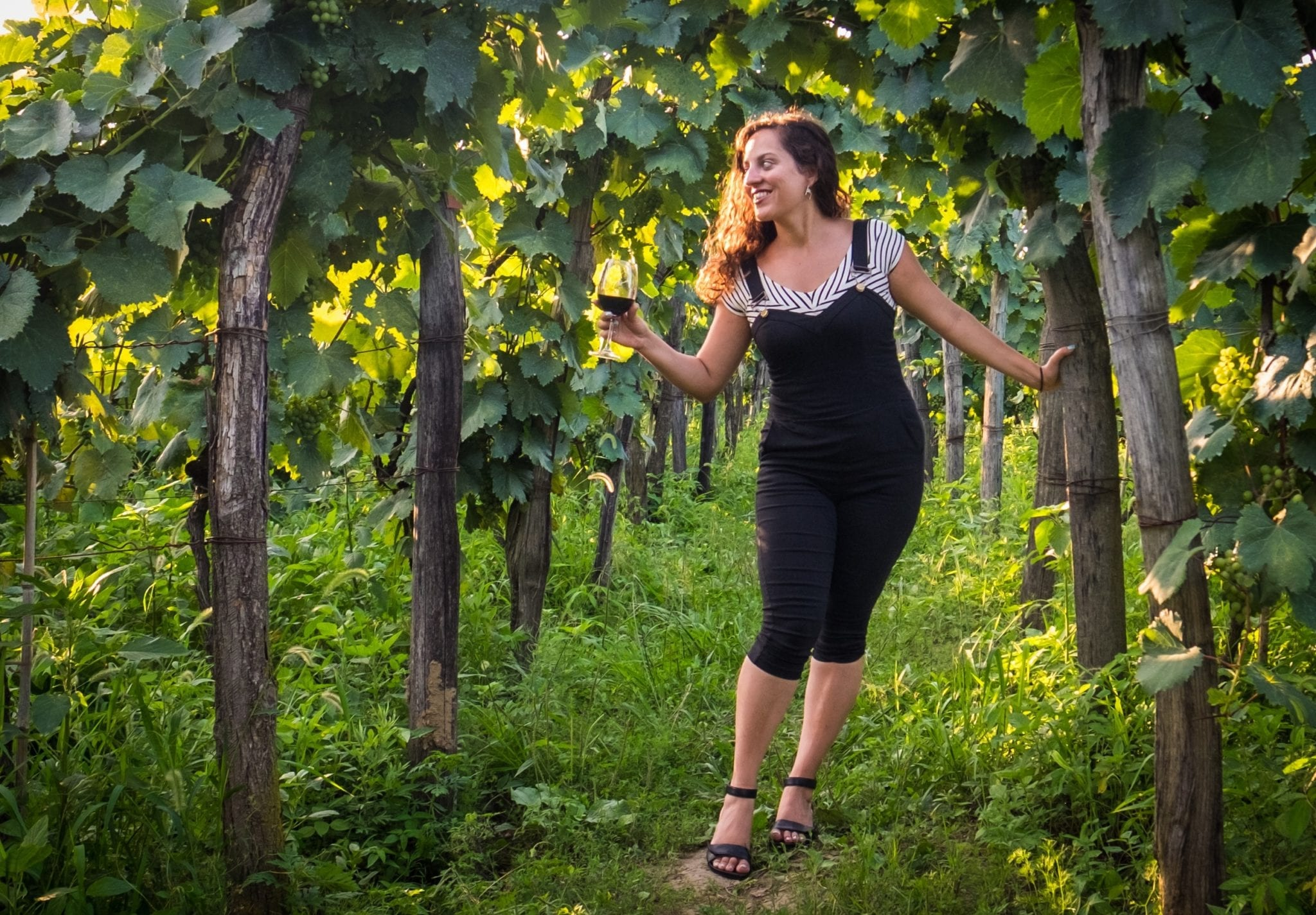 Kate stands in between lines of a vineyard, wearing cropped black overalls and hanging onto a wooden post and smiling as she holds a glass of wine in the other hand.