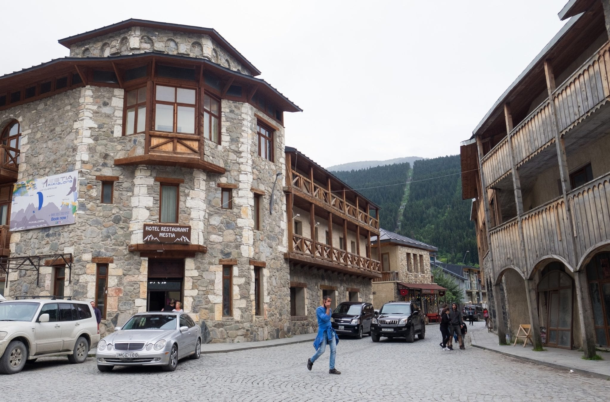A man walking across the street surrounded by stone-and-wood buildings in Mestia town.