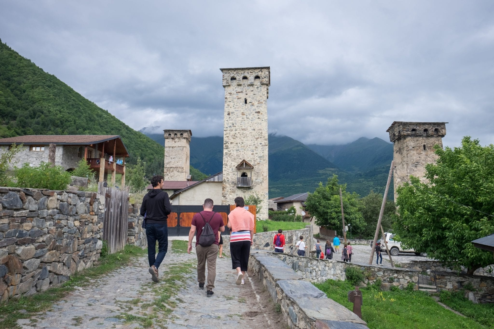 A group of bloggers walking toward one of the large stone towers, cloudy sky overhead.