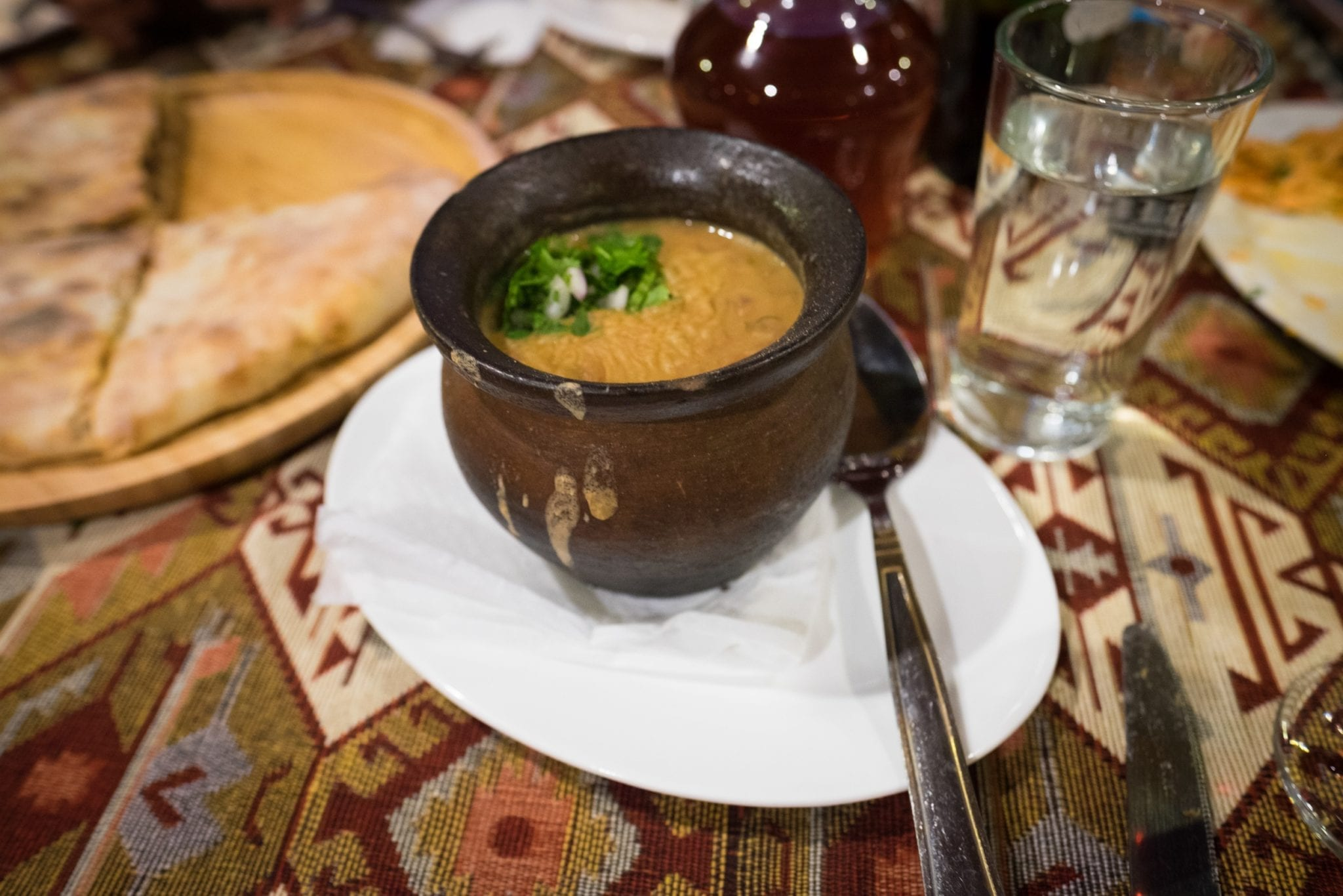 A dark brown vase-like bowl filled with lobio, Georgian stewed beans, sitting on a white plate.