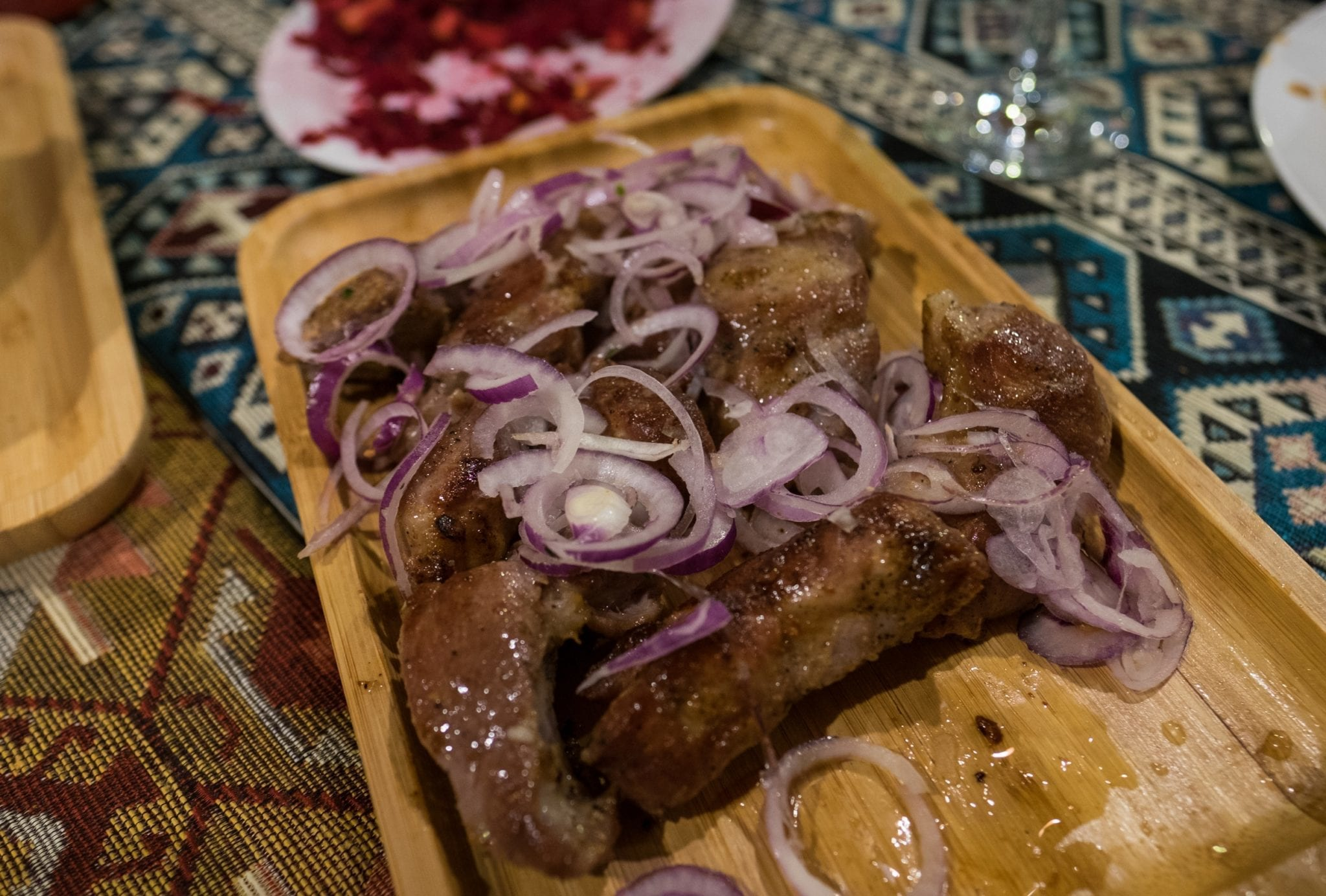 A wooden platter topped with (probably overcooked) pork strips, topped with raw red onions.