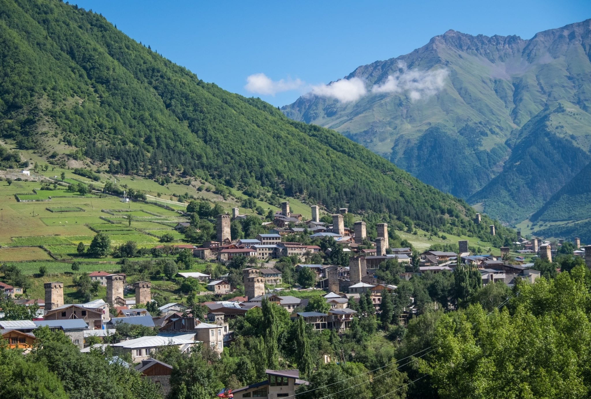 A village of stone towers in the foreground and mountains in the background in Mestia, Svaneti.