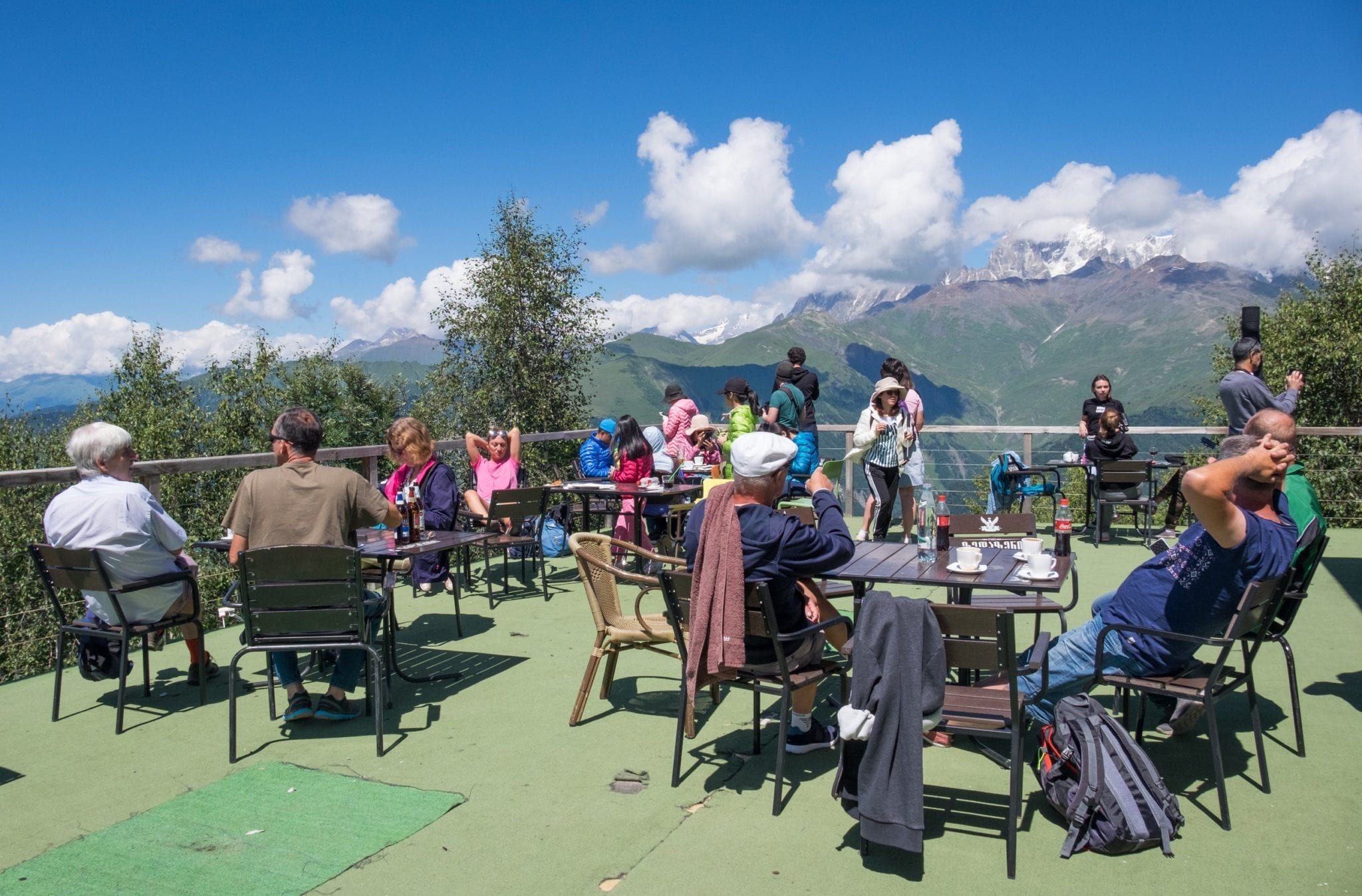 People eating outside at tables on a patio overlooking the mountains of Svaneti.