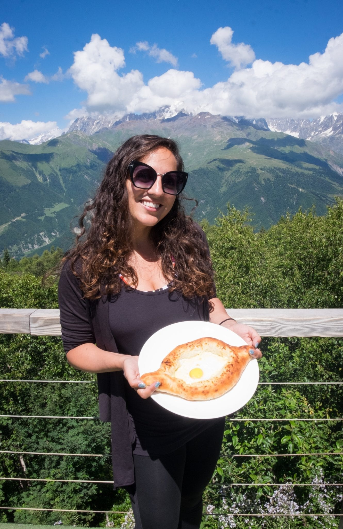 Kate stands in front of a Mountain View and holds a plate topped with a khachapuri -- a boat-shaped bread pastry with cheese and a fried egg on top.