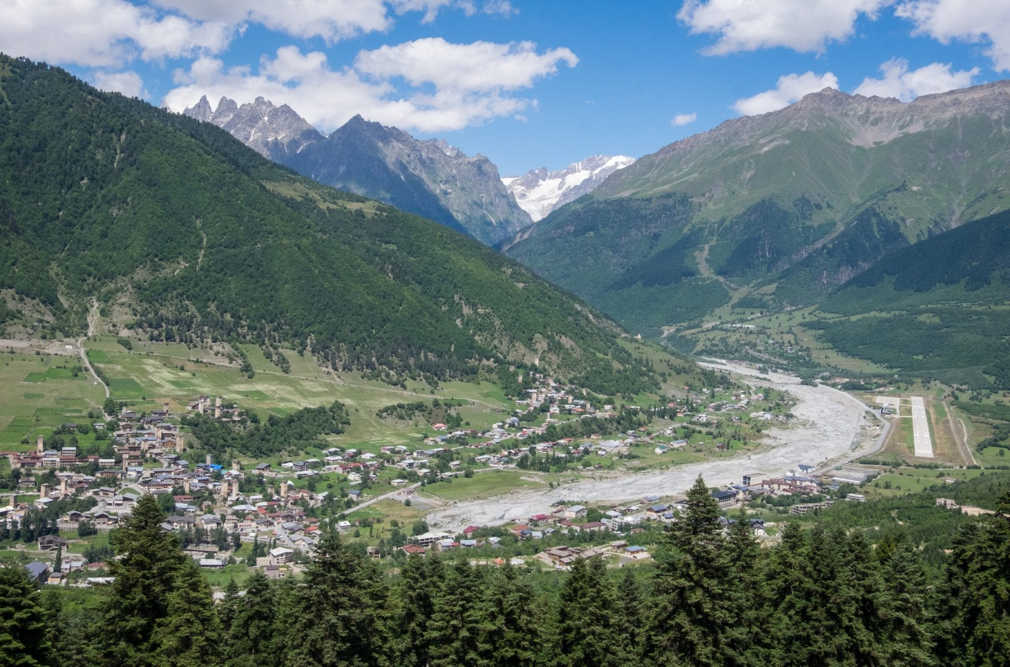 A view over the town of Mestia in Svaneti -- huge mountains underneath a blue sky; evergreen trees along the bottom, and a village full of stone towers.