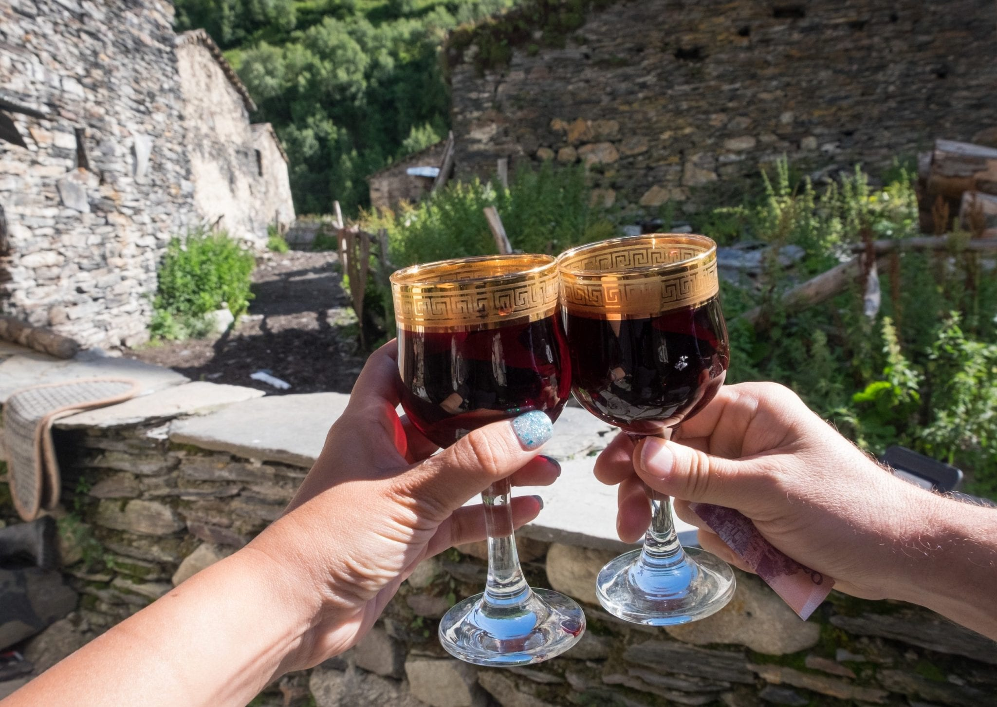 Two hands holding up tiny wine glasses edged with gold, each holding red wine, stone buildings in the distance.