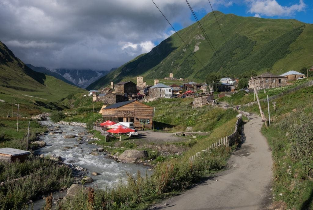 A path leading past a stream in Ushguli, leading to guesthouses and cafes with green mountains in the distance.