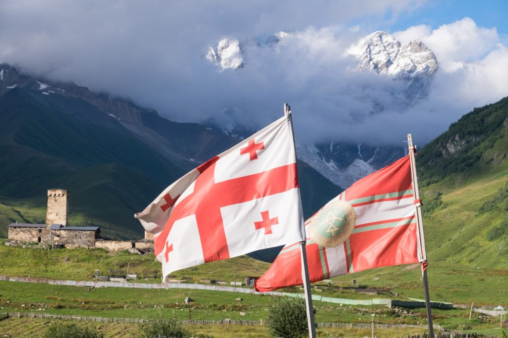 The Georgian flag and the Svaneti flag, both red and white, flying side by side with the mountains and stone towers of Ushguli in the background.