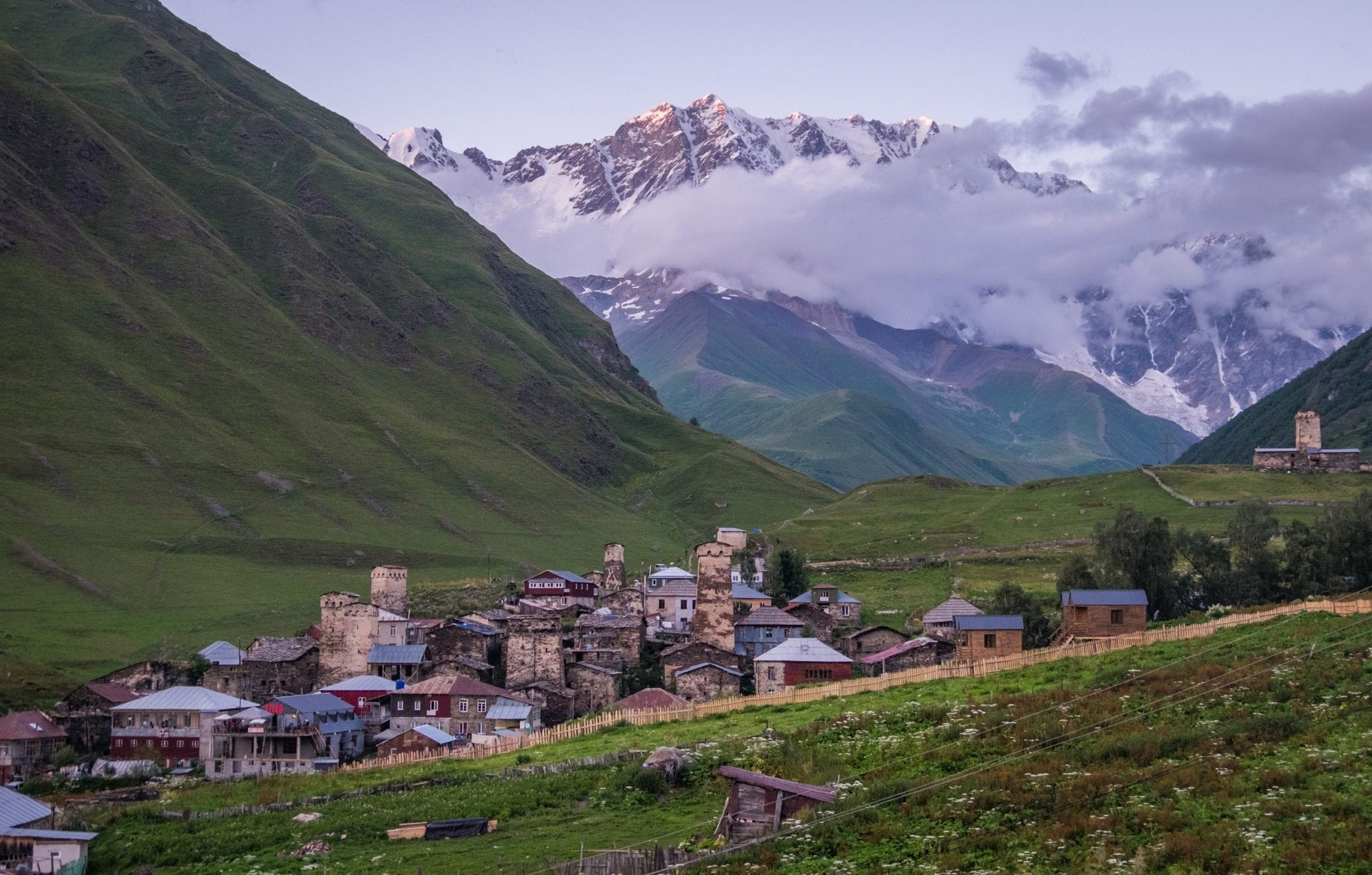At dusk, the village of Ushguli looking purple in the evening light, surrounded by hills, purple mountains covered by clouds in the background.