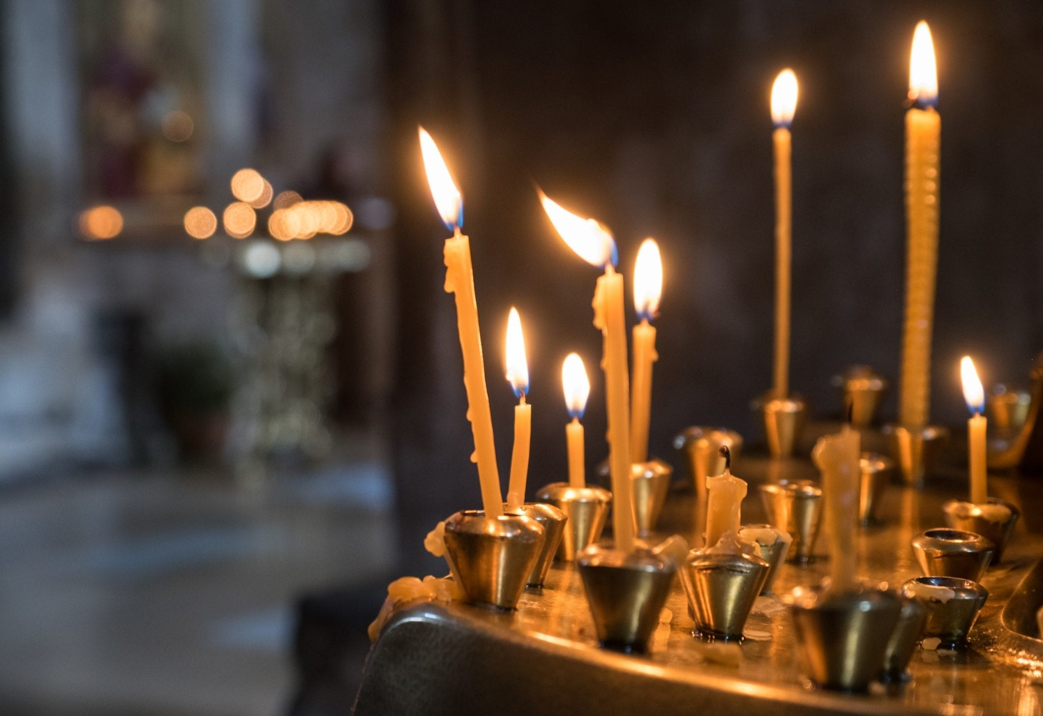 Tall, skinny yellow candles burning on a gold offering table in a church in Mtskheta, Georgia.