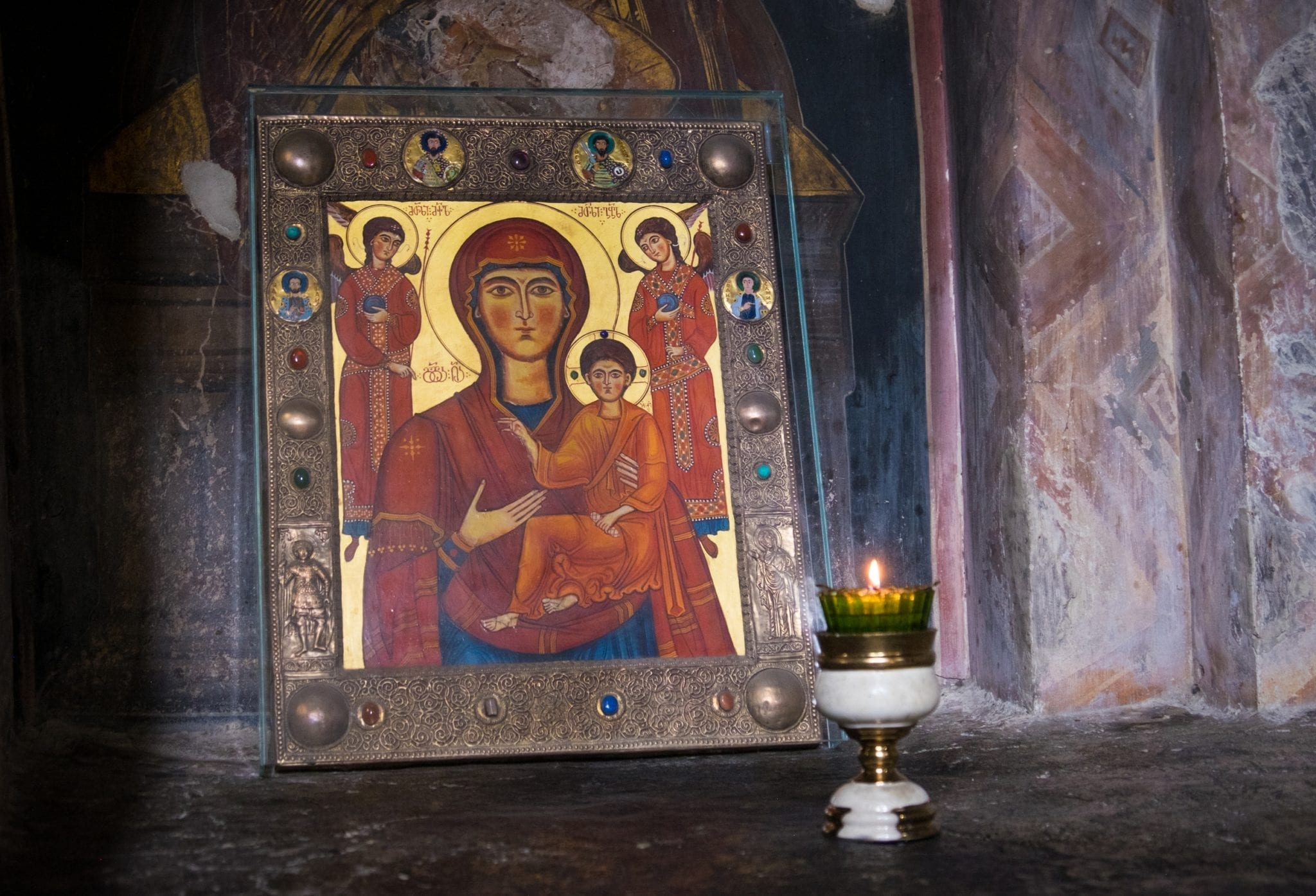 A gold portrait of the Virgin Mary and Jesus leaning against a wall in a Georgian church, a chalice sitting in front.