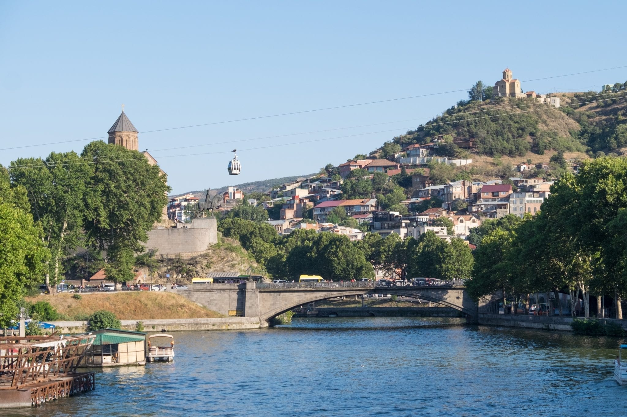 A shot over the river in Tbilisi, bridges crossing it. On the right is a monastery perched on a hill and you see a cable car traveling a wire in the air.