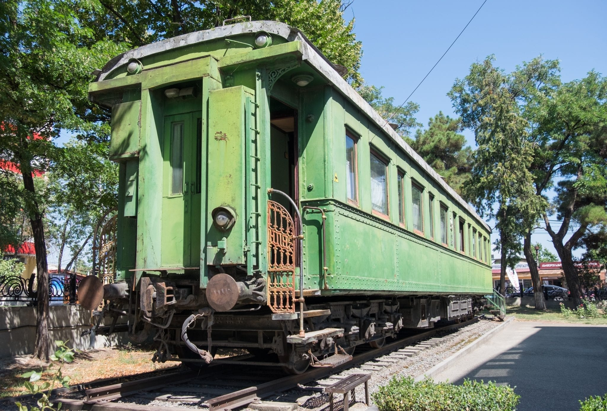 A bright green train car sitting on tracks. The train was Stalin's.