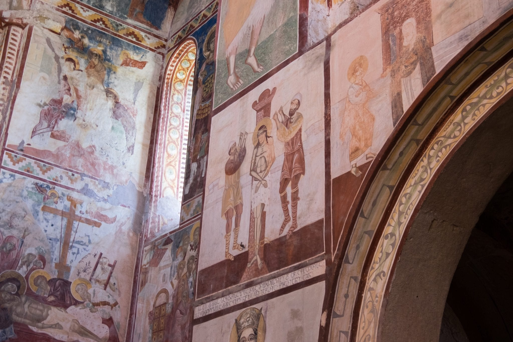 Interior of Gelati Monastery with earth-colored frescoes of sacred scenes in the Bible painted on the walls.