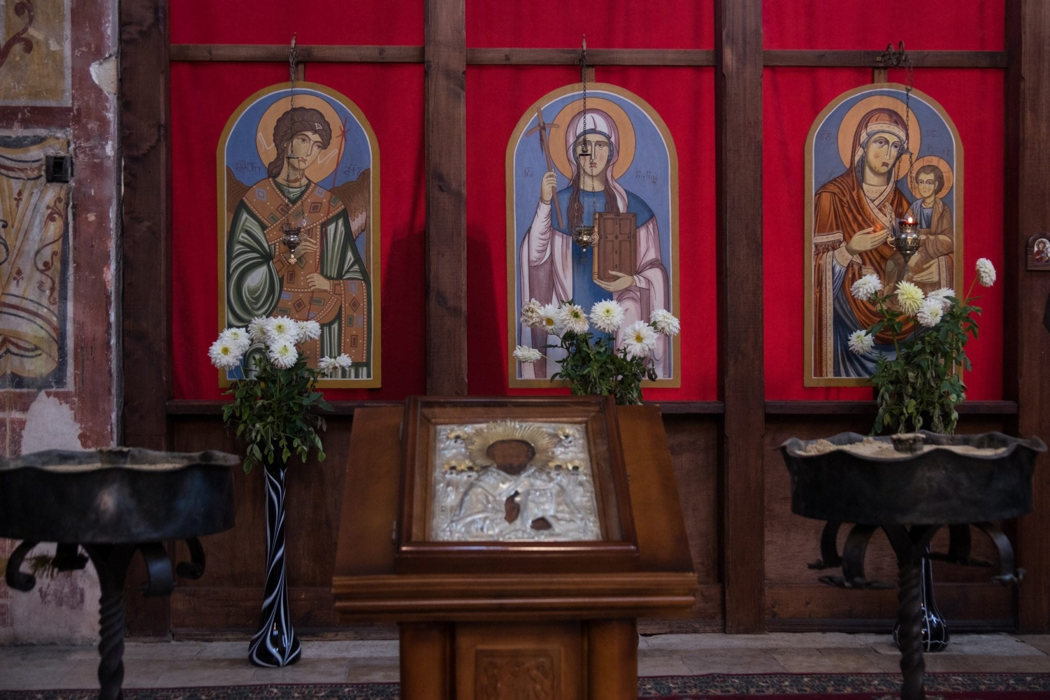 The altar at Gelati Monastery, with pictures of saints in front of blood-colored paneling.