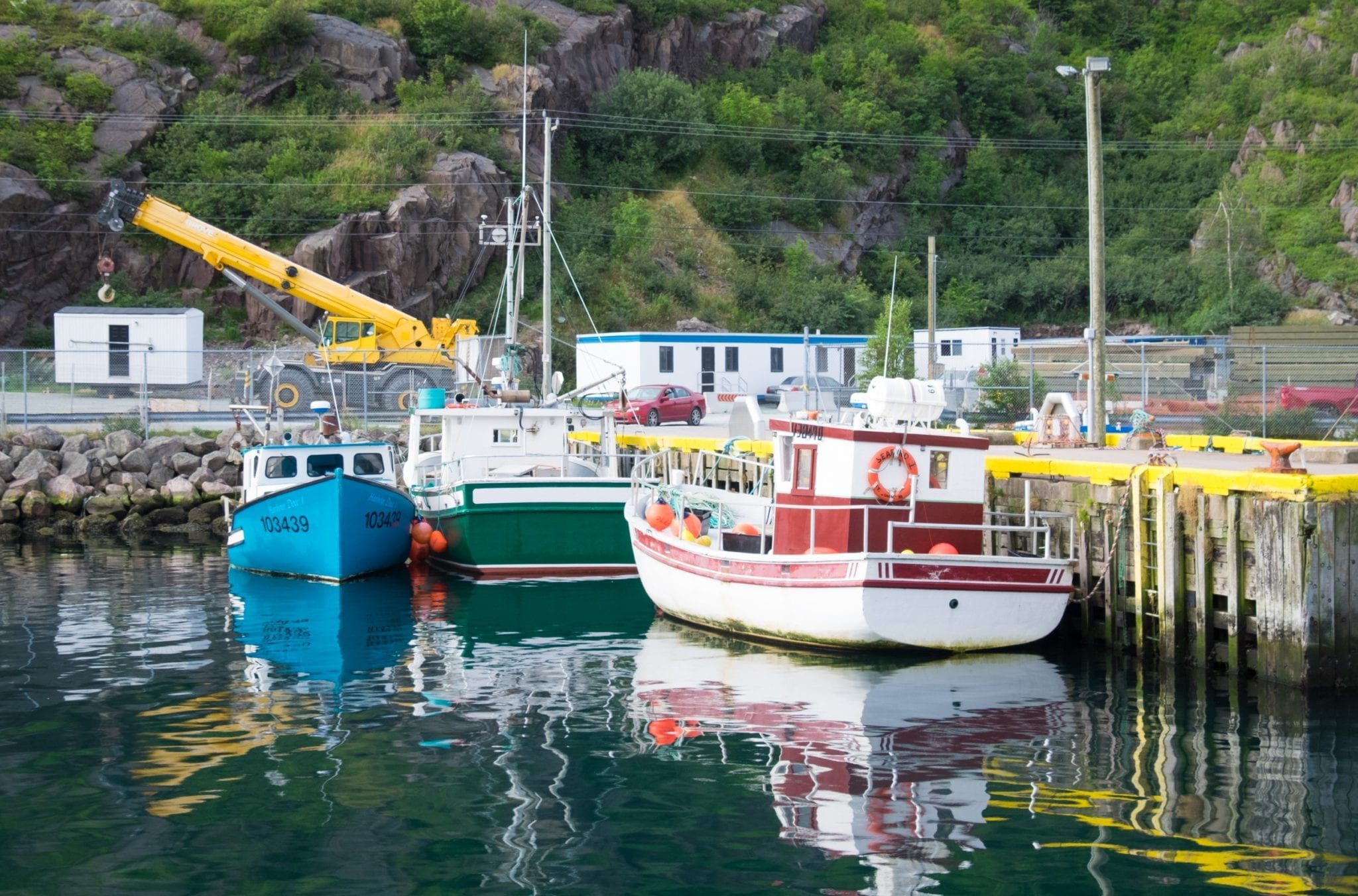 Boats sitting on a glassy teal harbor in Newfoundland.