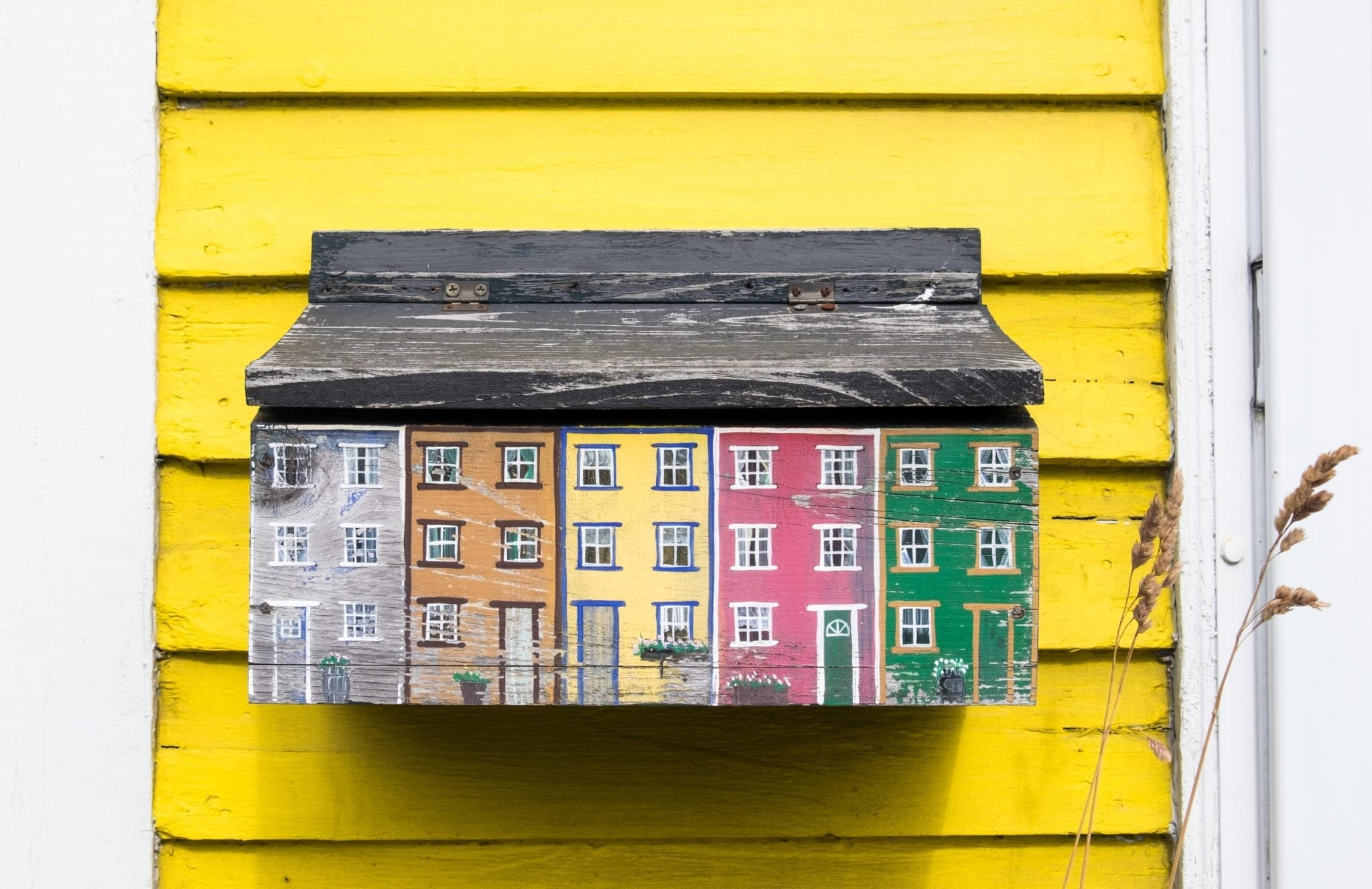 A mailbox shaped and painted like the houses of Jelly Bean Row, attached to a yellow house.