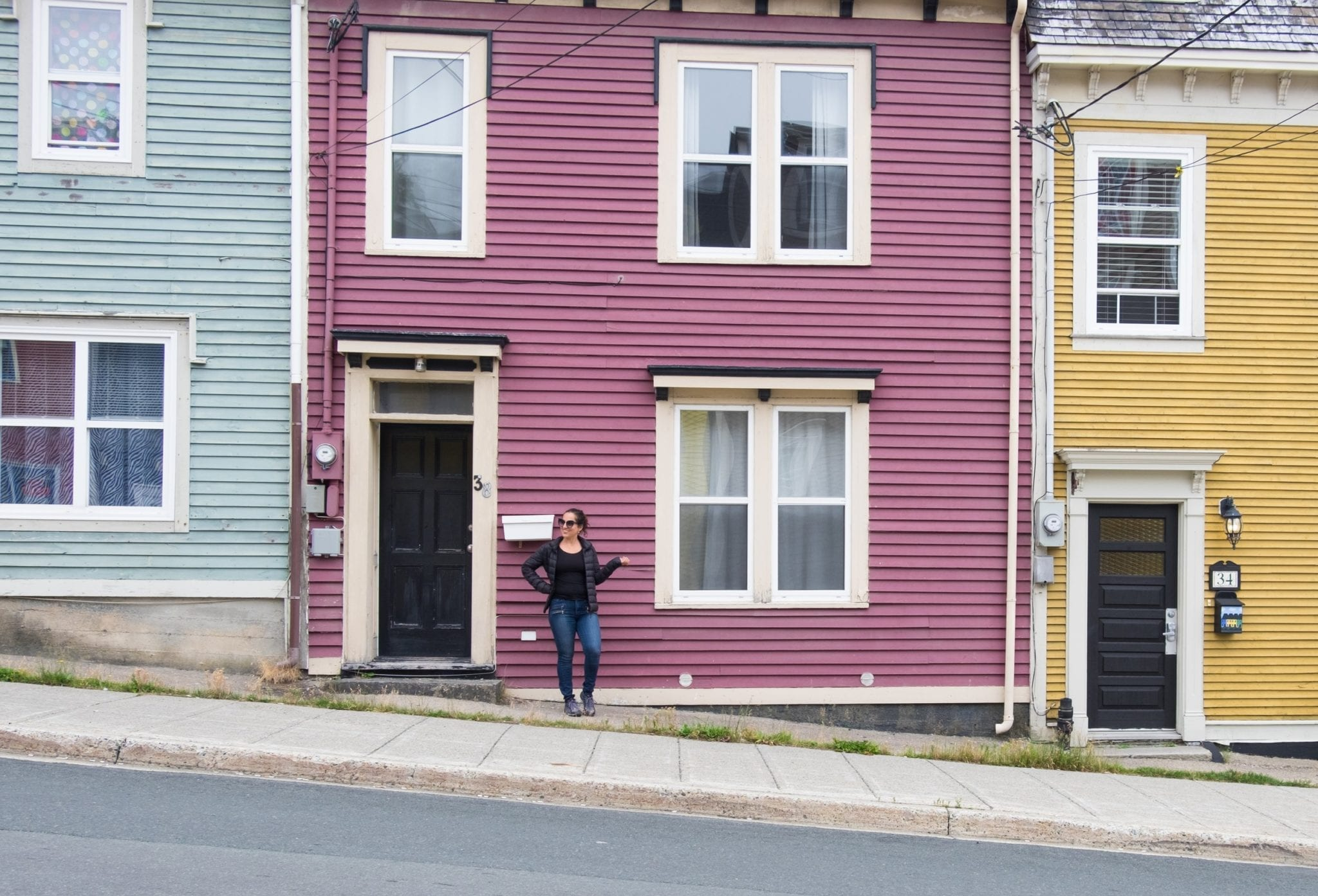 Kate stands in front of a mauve house with a pale blue house on the left and a mustard yellow house on the right.