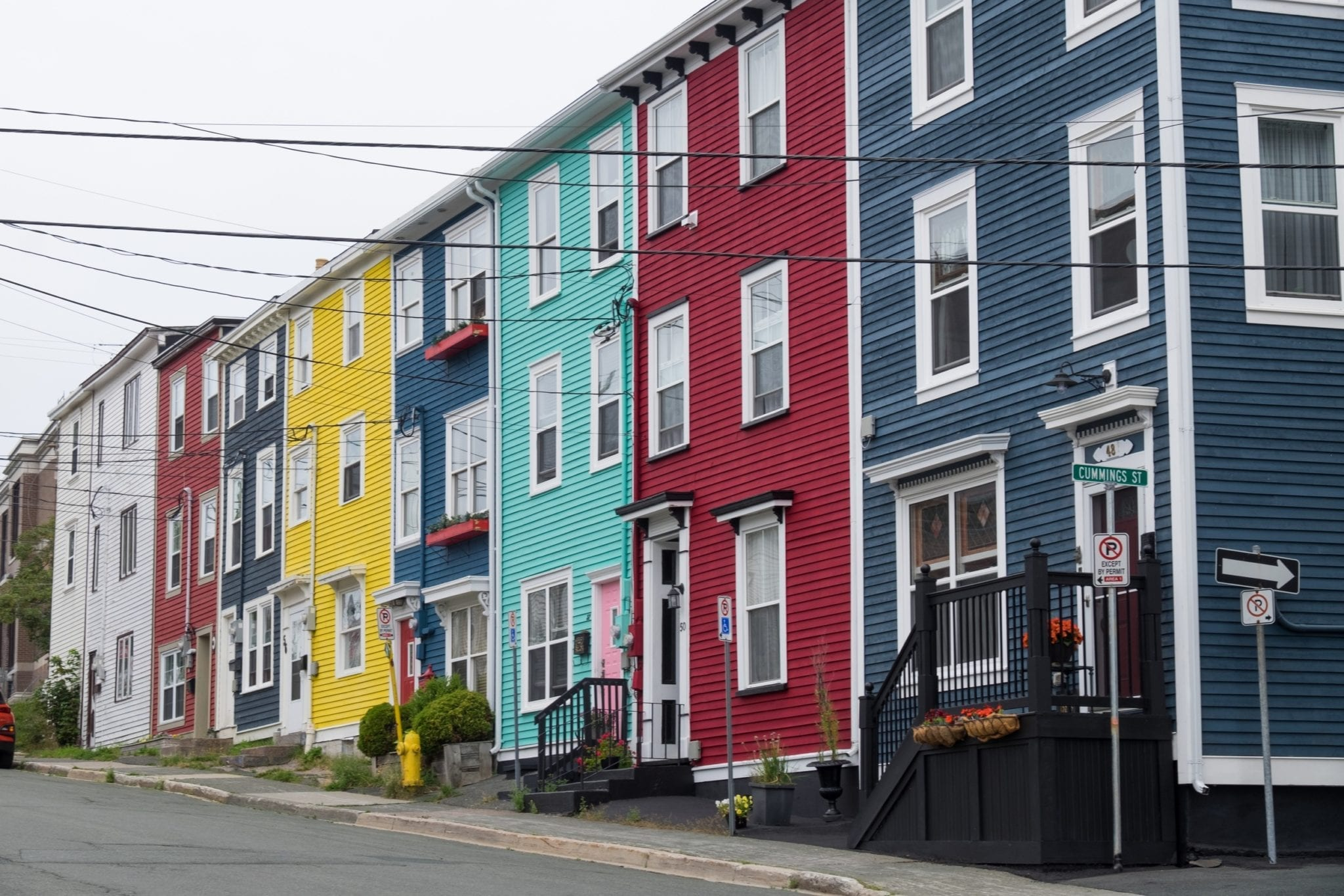 A row of brightly colored square houses in St. John's: yellowfins, blue, sea green, burgundy, and navy.