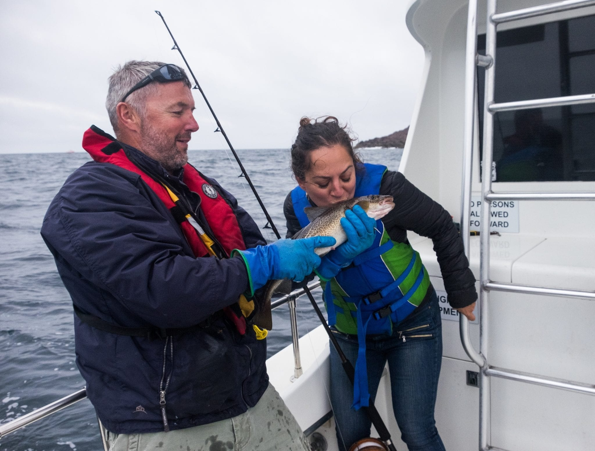 A fisherman holds up a cod for Kate and she leans in and kisses it.