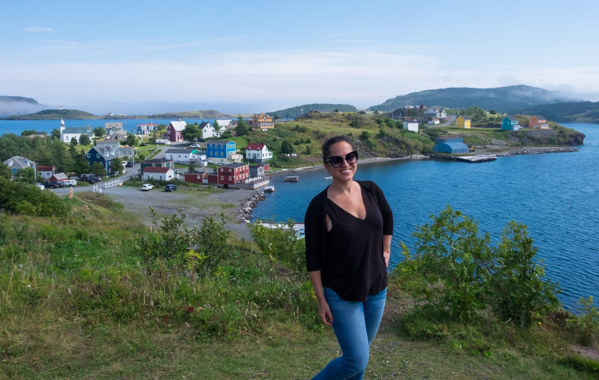 Kate stands in front of the a colorful village on a grassy peninsula surrounded by a bright blue bay.