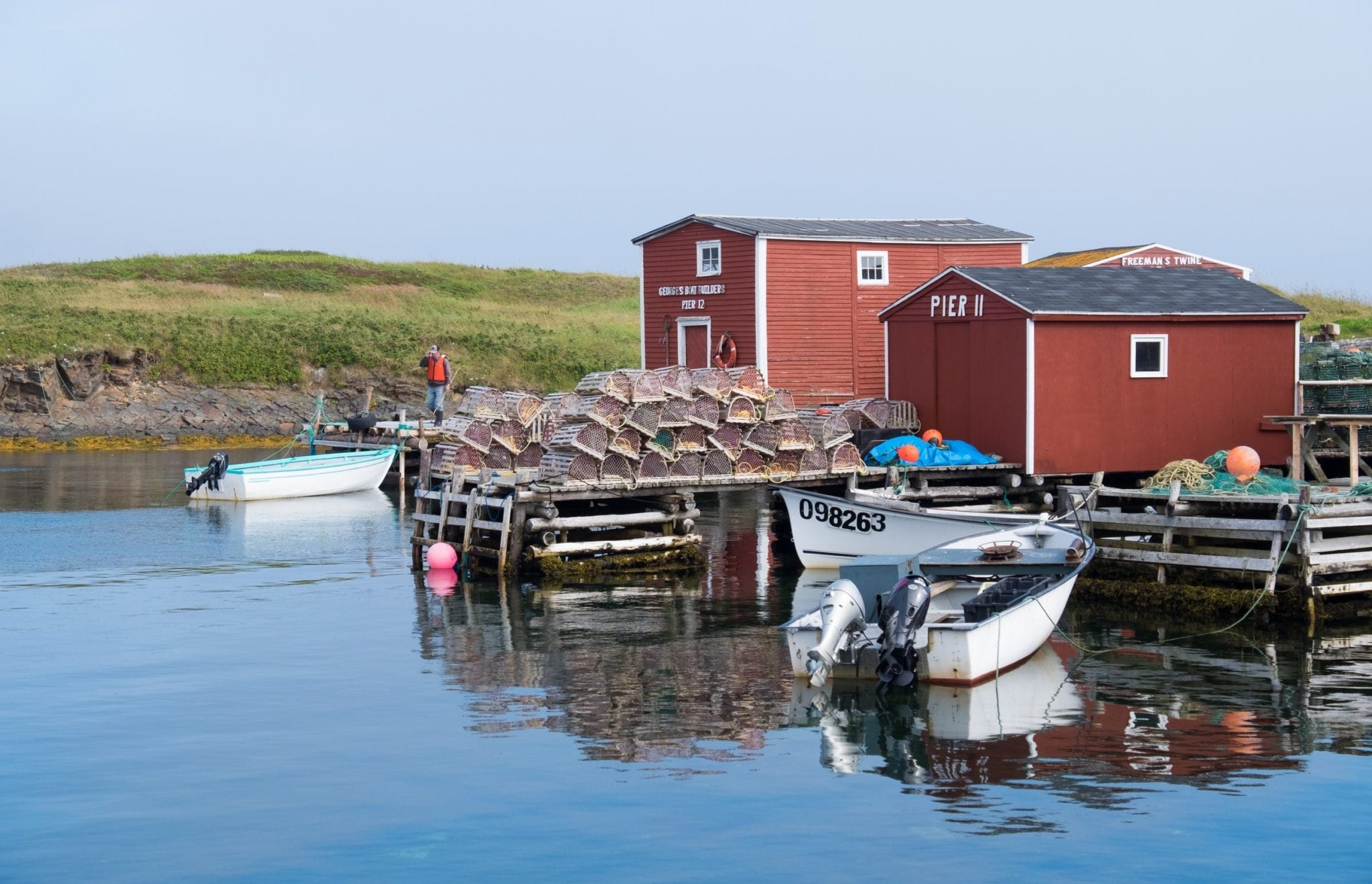 Red fishing cottages perched on the glassy blue bay next to lobster traps in Newfoundland.