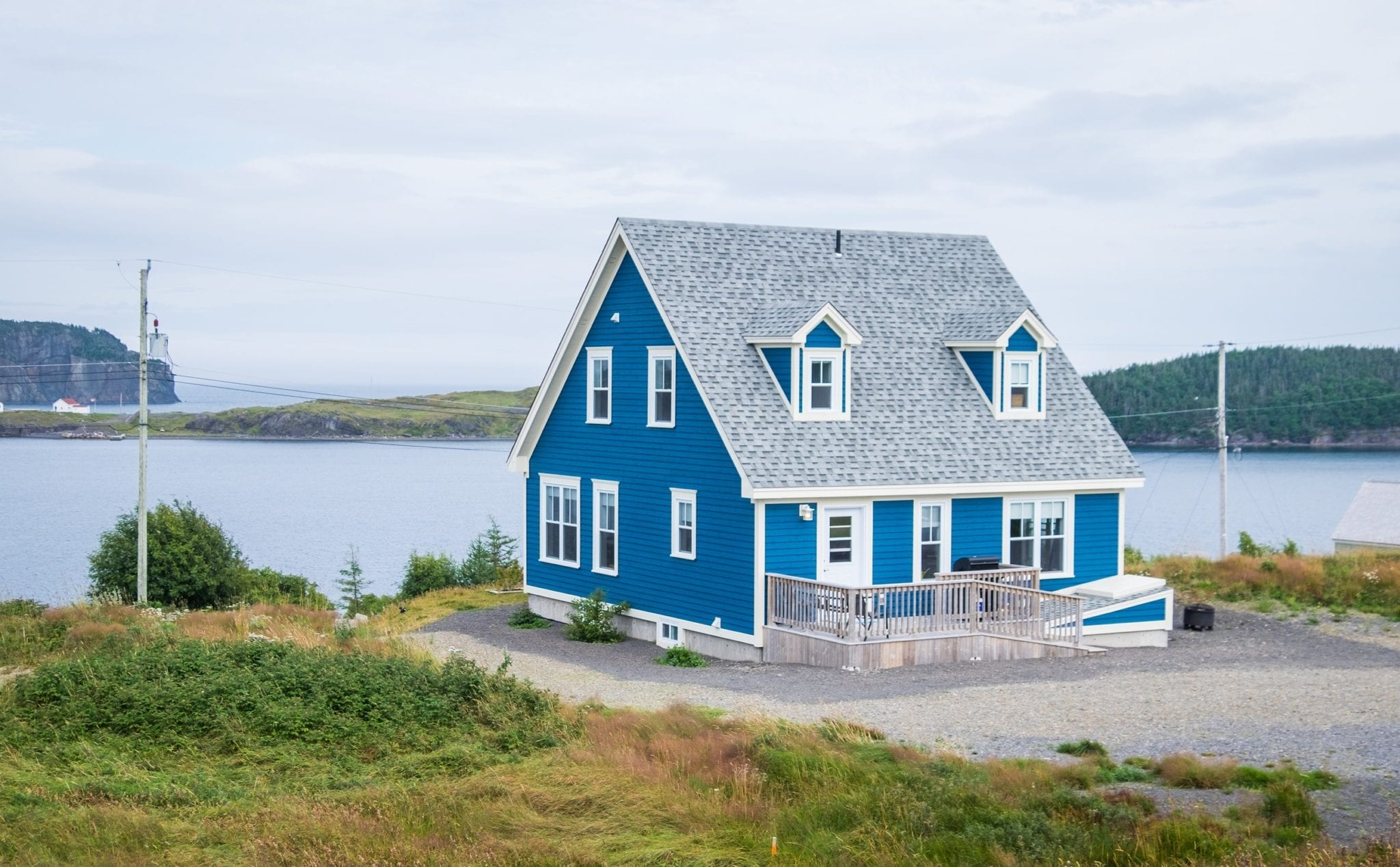 A deep blue cottage perched on the edge of the bay in Trinity, Newfoundland